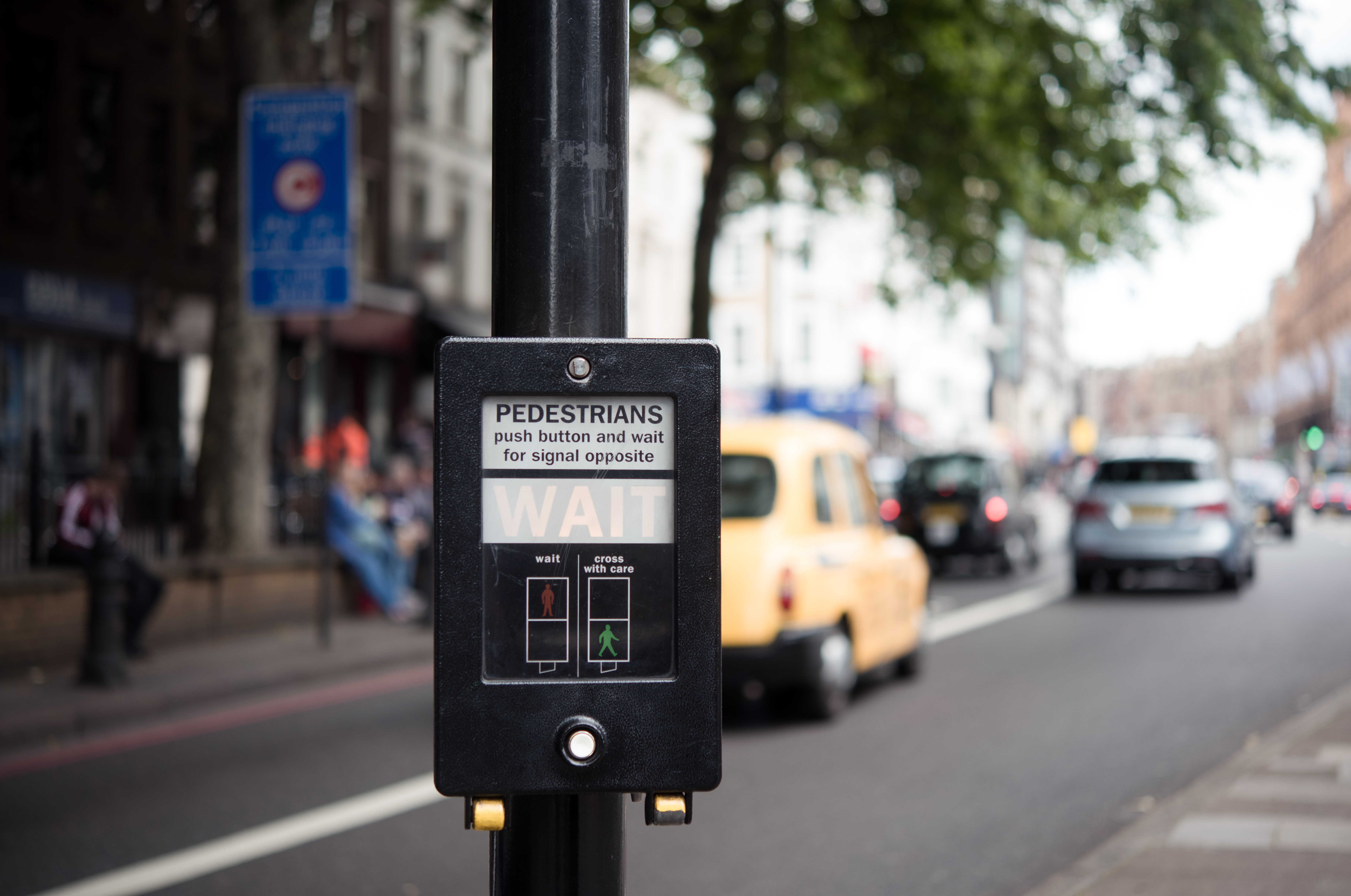 Pedestrian crosswalk button on a busy street in London