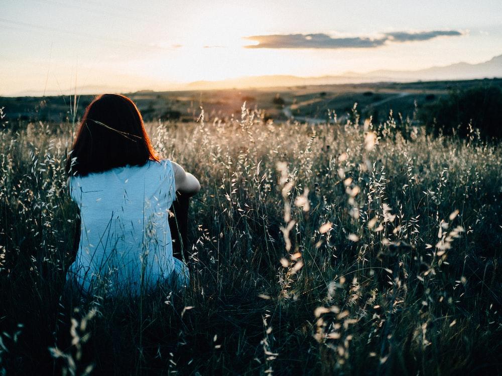 woman sitting on grass field watching sunset