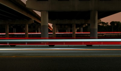 timelapse photography of vehicle light crossing on road under concrete dock long exposure teams background