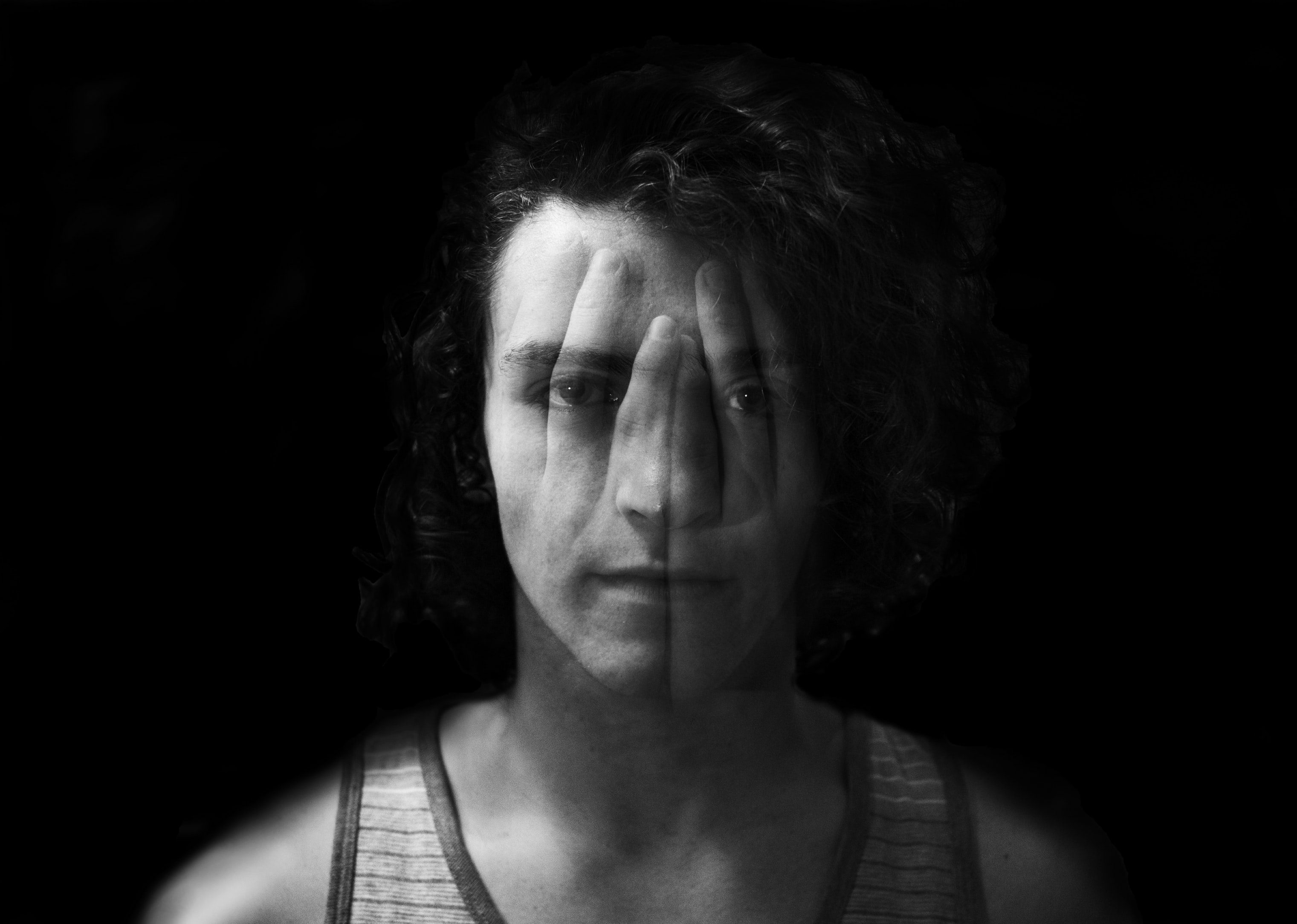 A person with the silhouette of hands on their face, against a black background