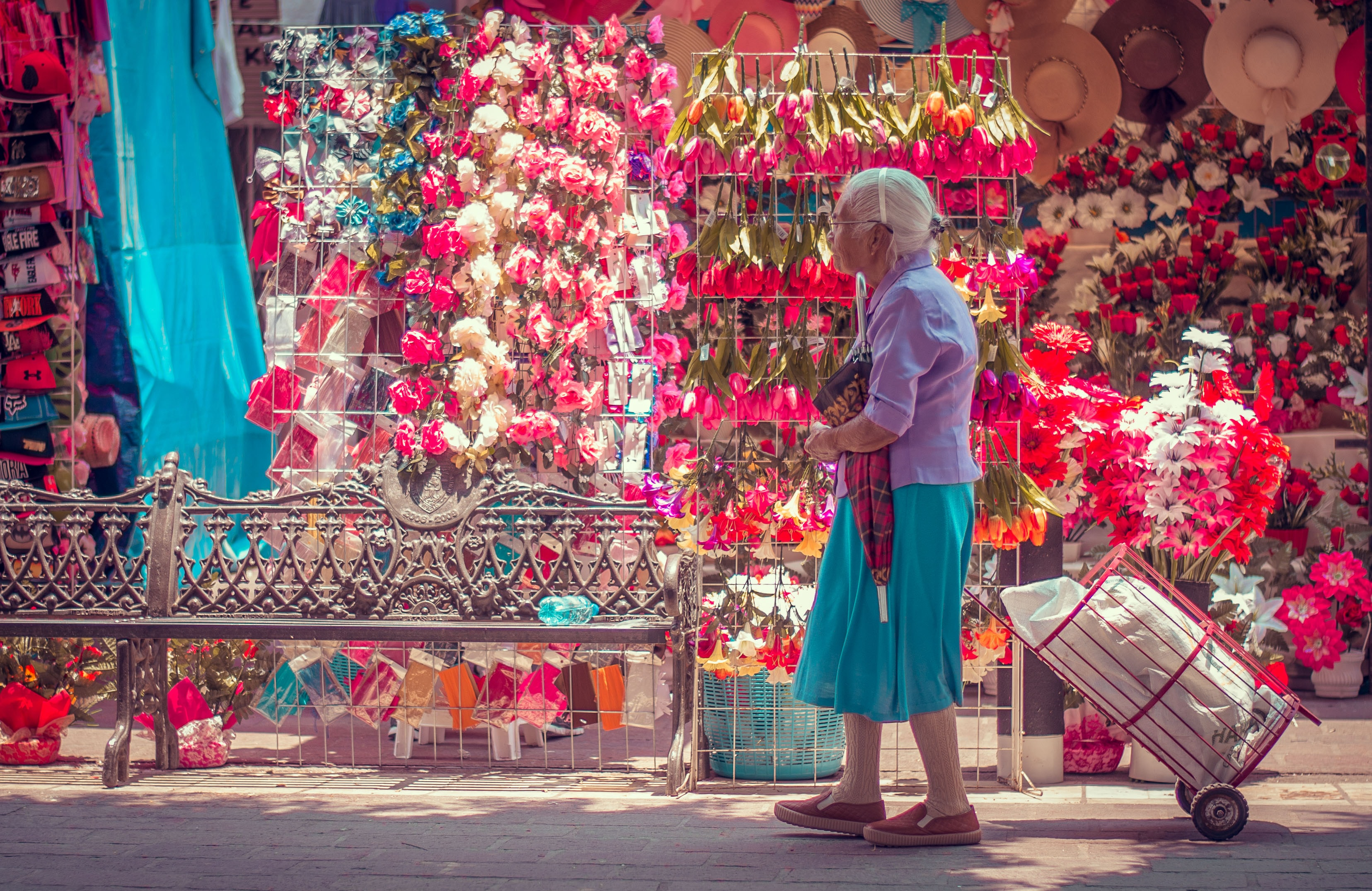 An older Asian woman with white hair pulling her cart along a flower vendor.