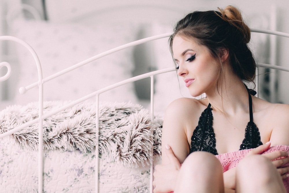 woman wearing black lingerie holding pink pillow