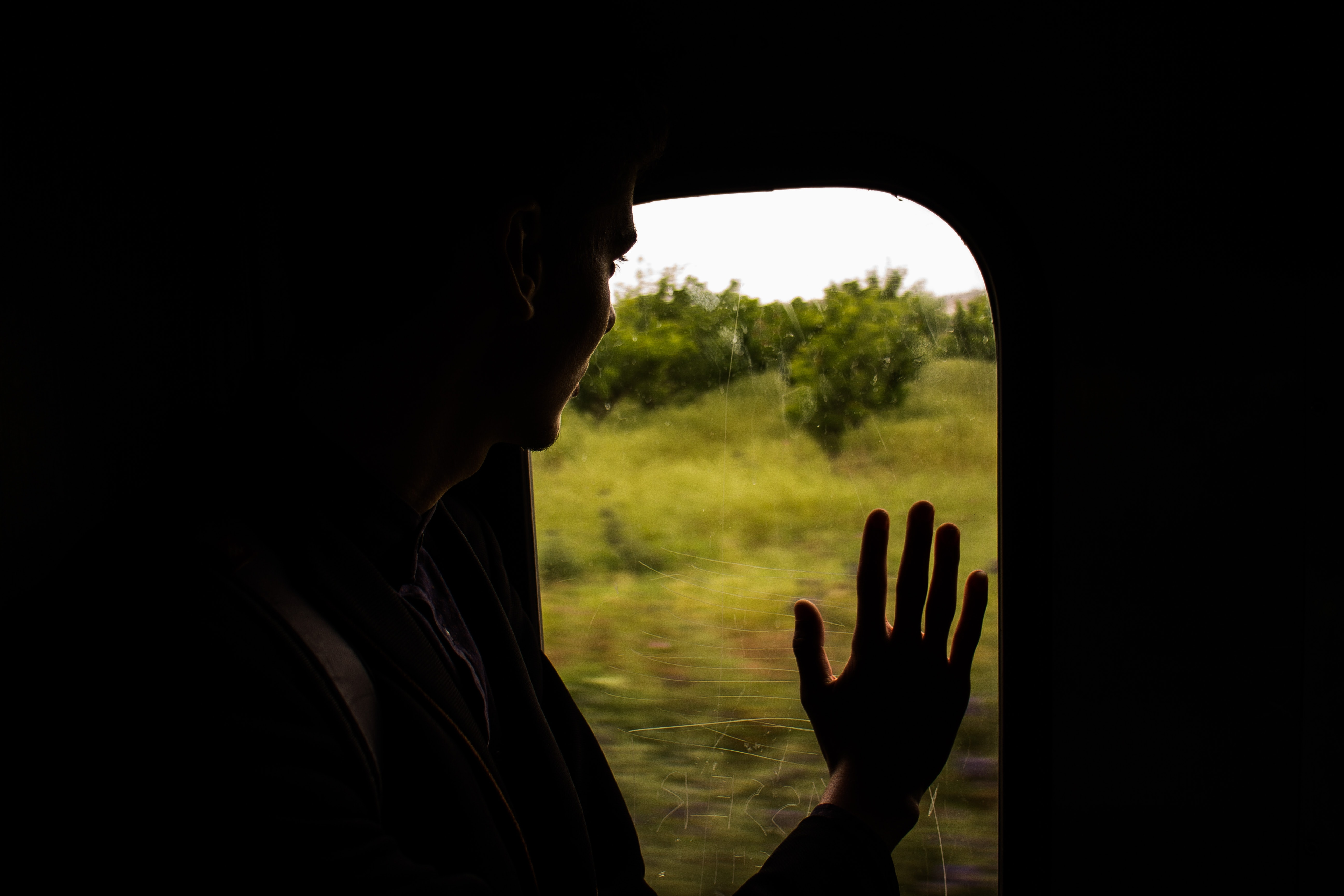 Man looking outside with hand on window and view of green landscape in Algeria