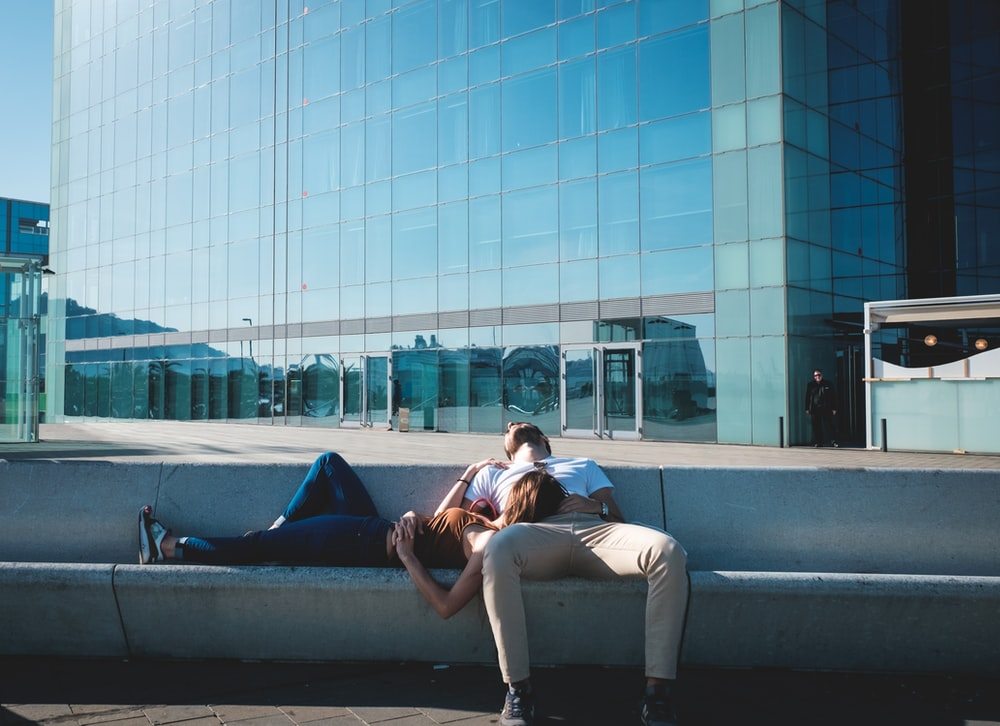 man and woman taking a nap on concrete stairs