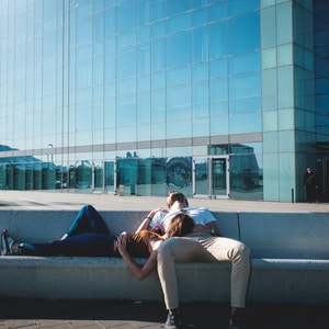 man and woman laying on concrete stairs