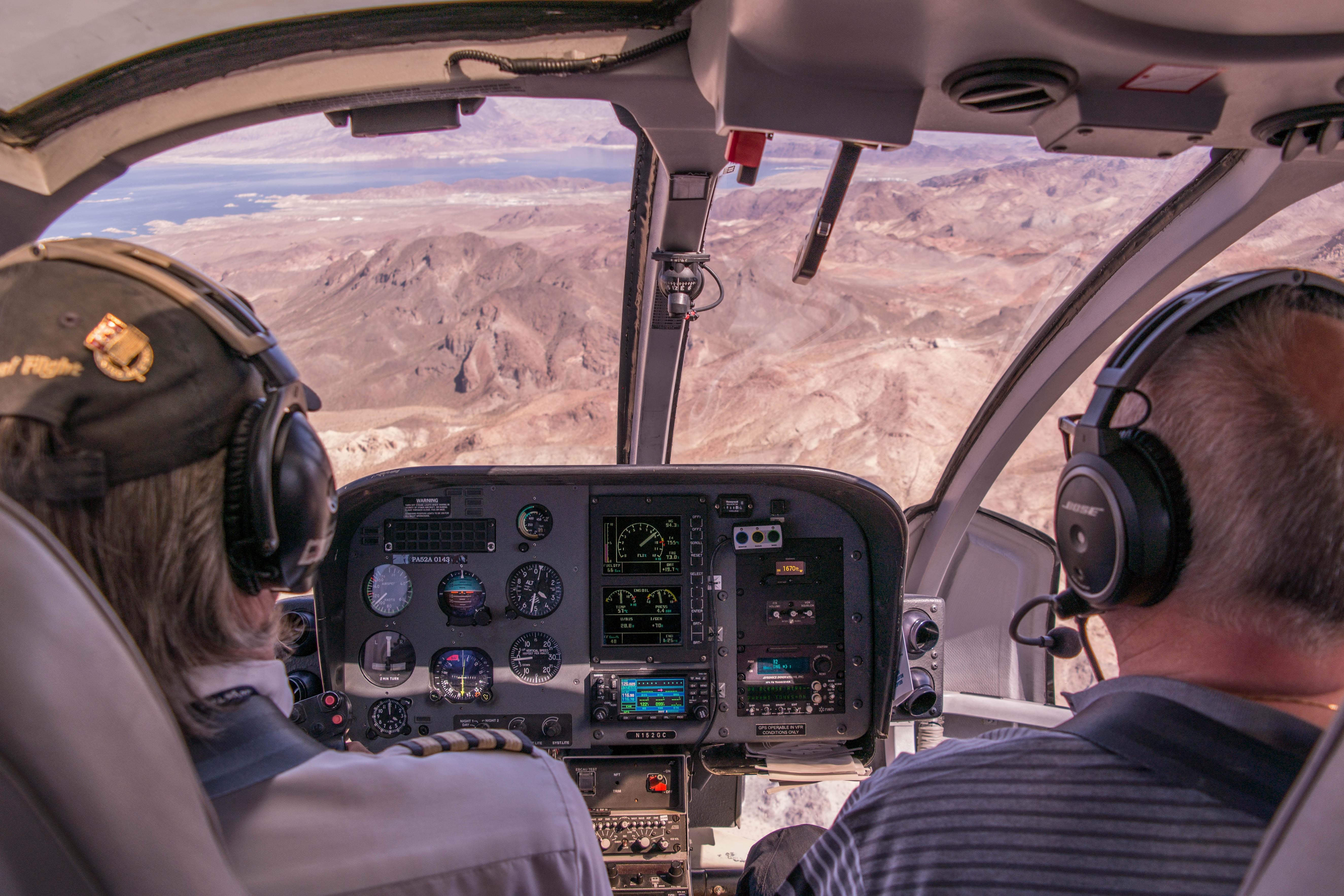 two person riding plane near mountains during daytime