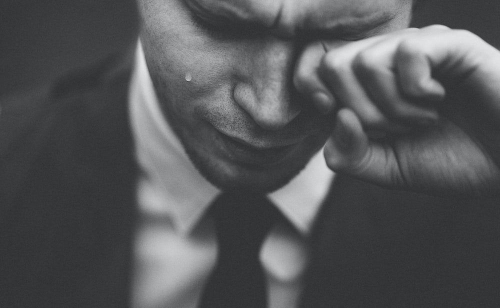 A black and white shot of a crying man in a suit and tie