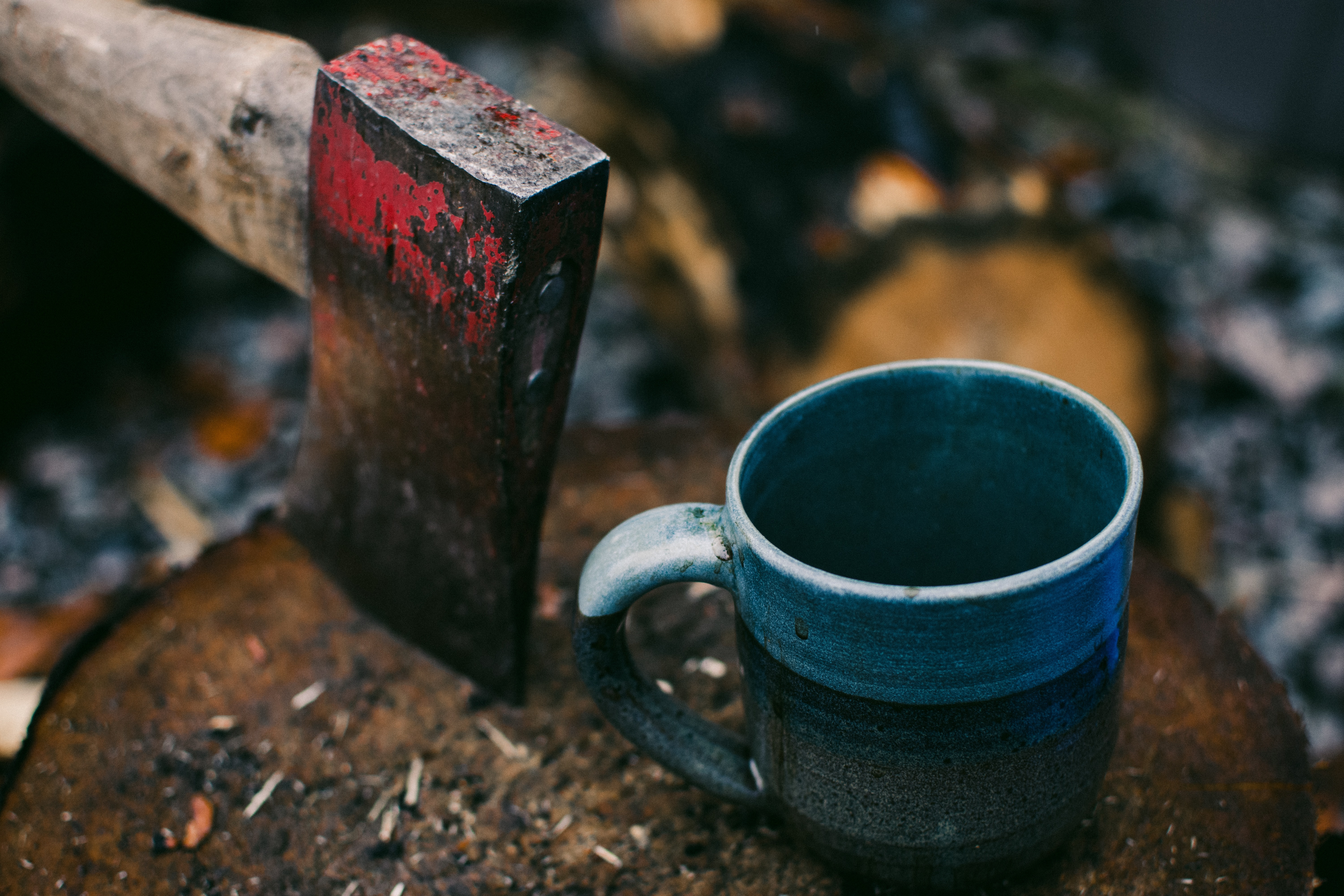 A blue enamel cup next to a rusty axe on a log