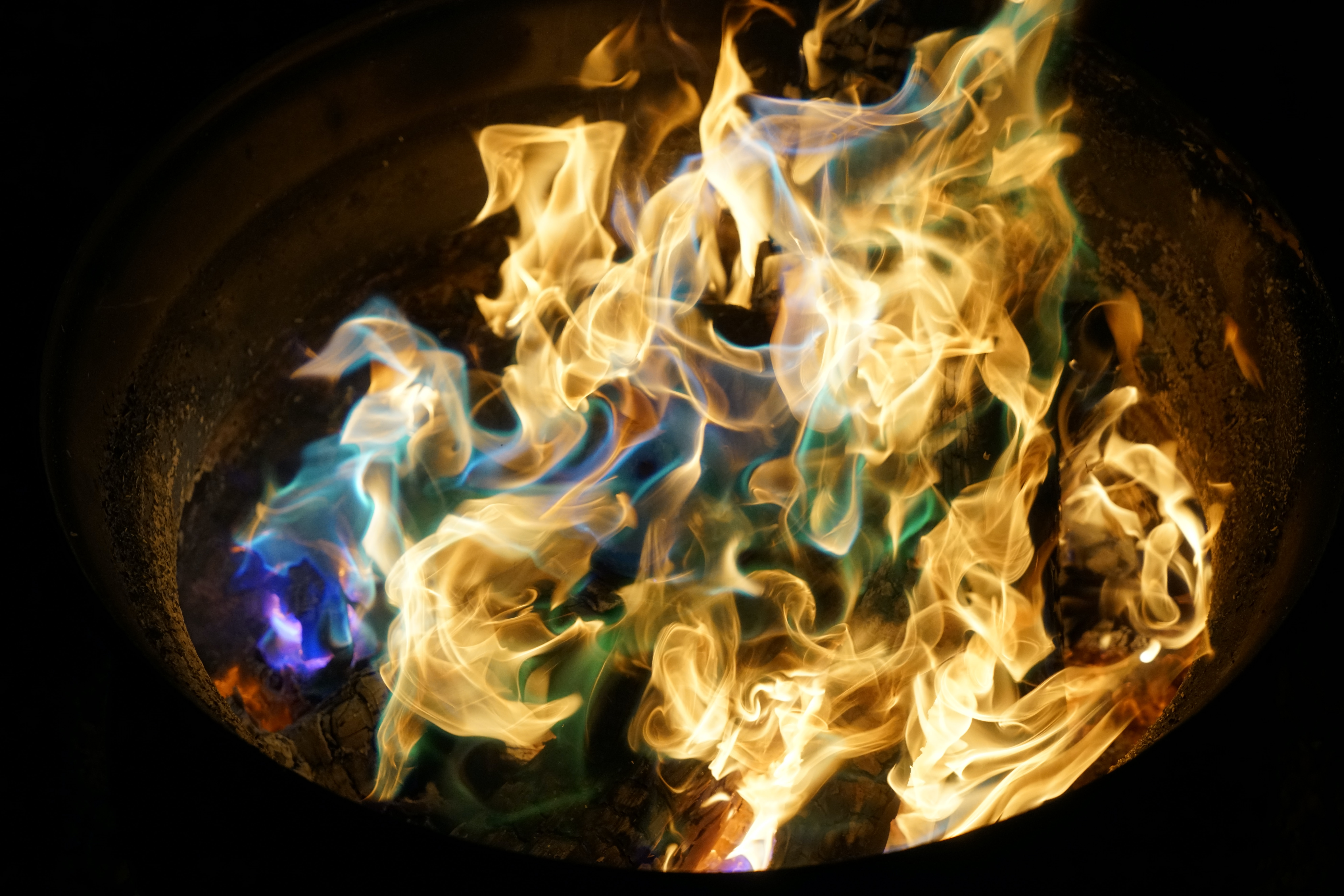 An orange fire with blue, purple, and green flames at night