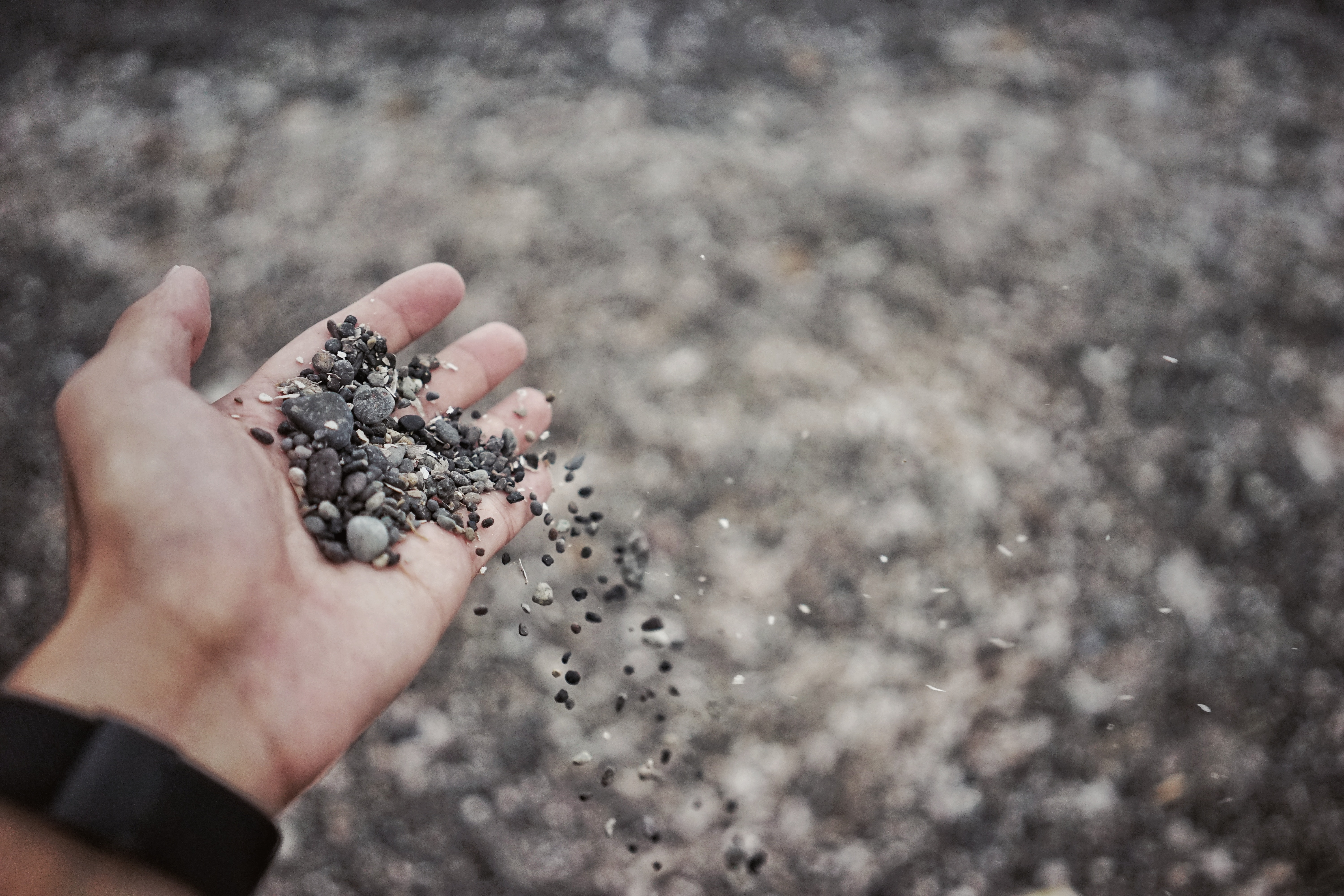 A person wearing a watch holding a bunch of gravel in their hand