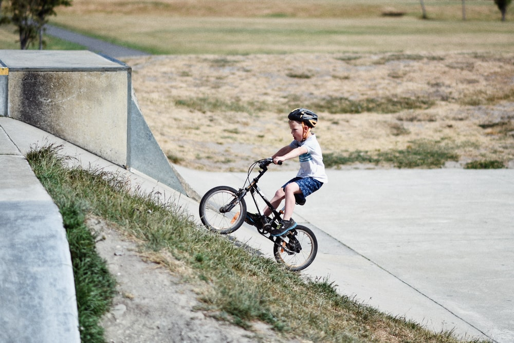 """5-year-old boy with a helmet riding a 14"""" kids bike"""
