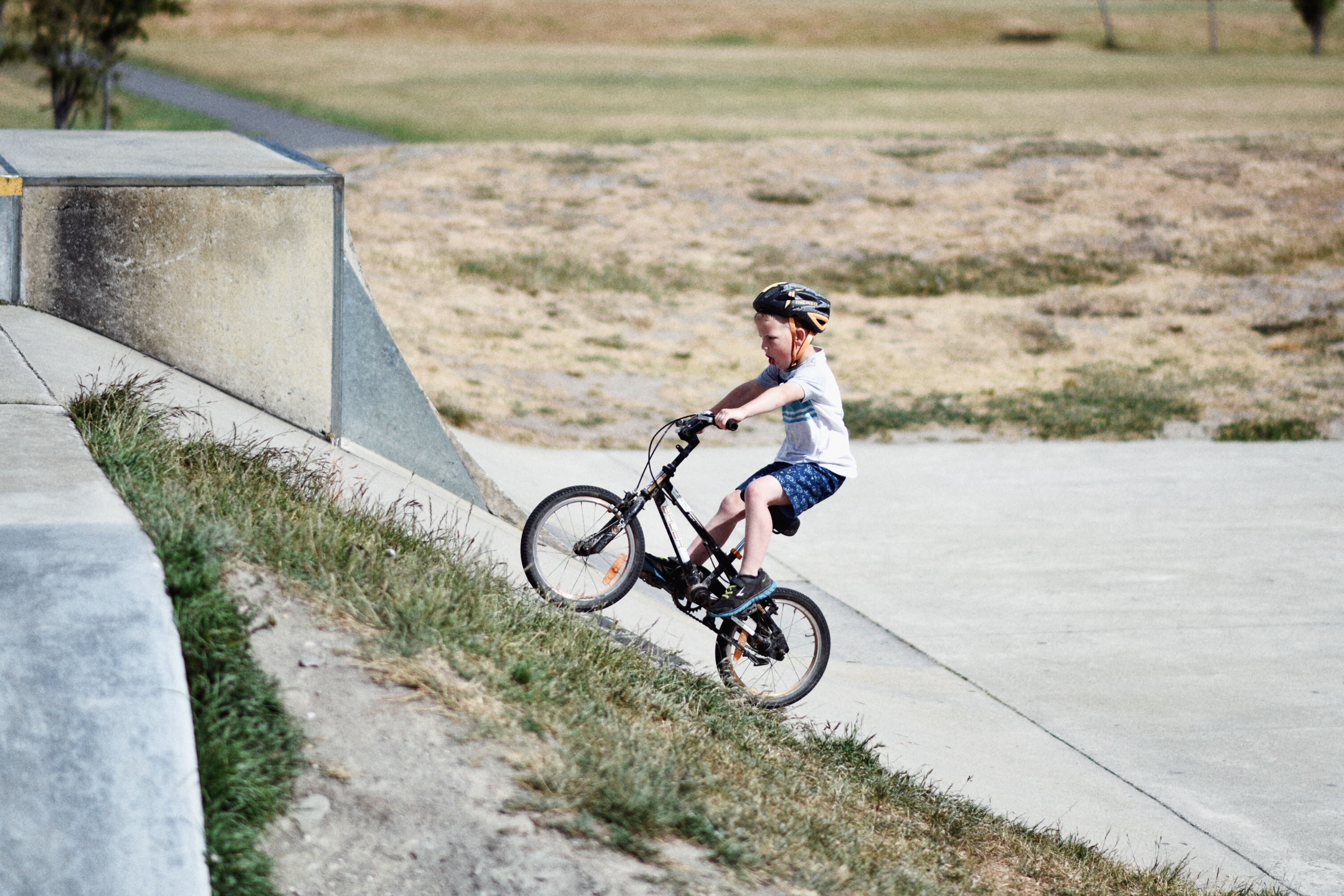 Child on bicycle in helmet on concrete ramp