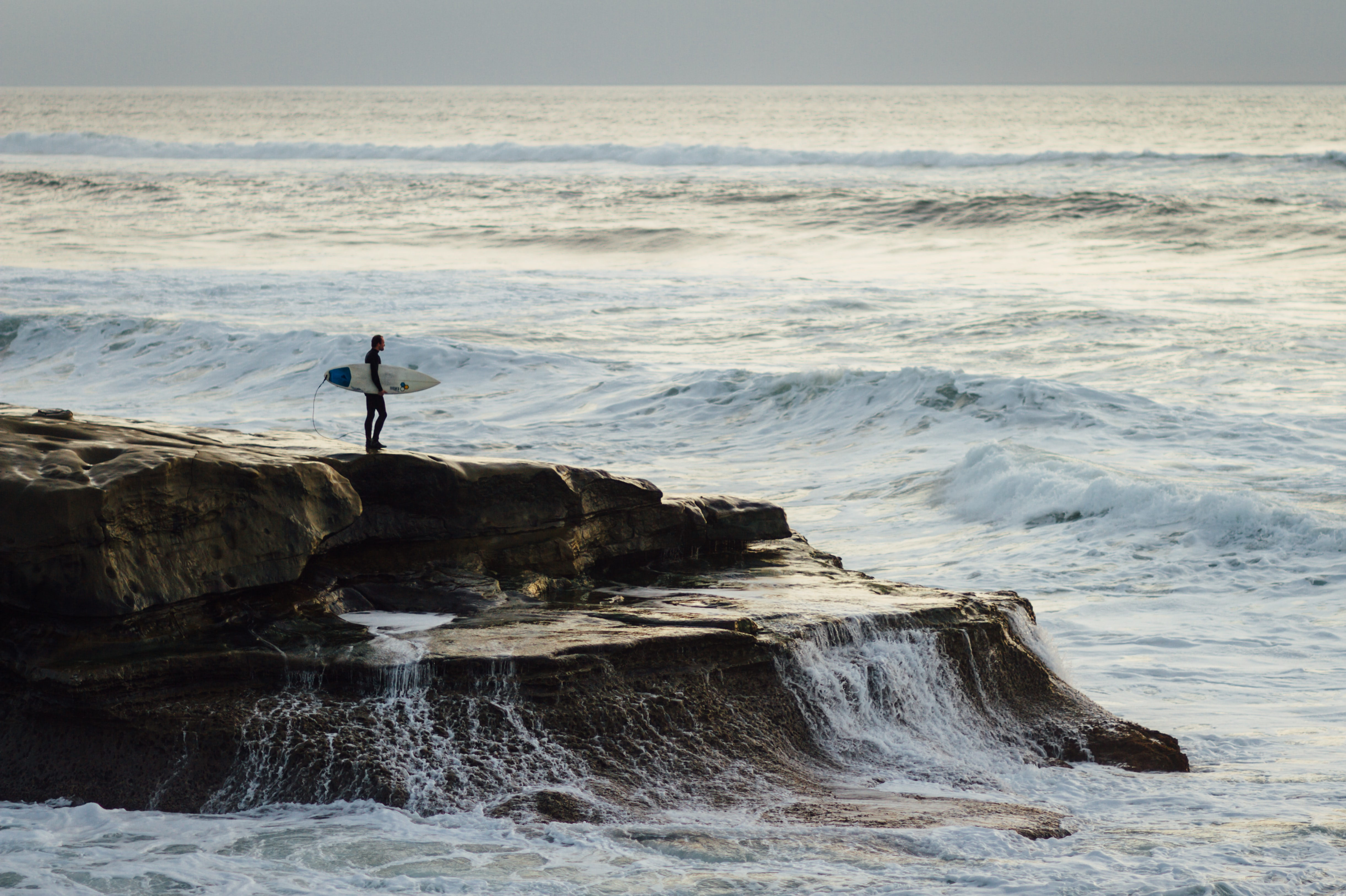 Surfer with a surfboard standing on a coastal rock watching rough ocean at Ocean Beach