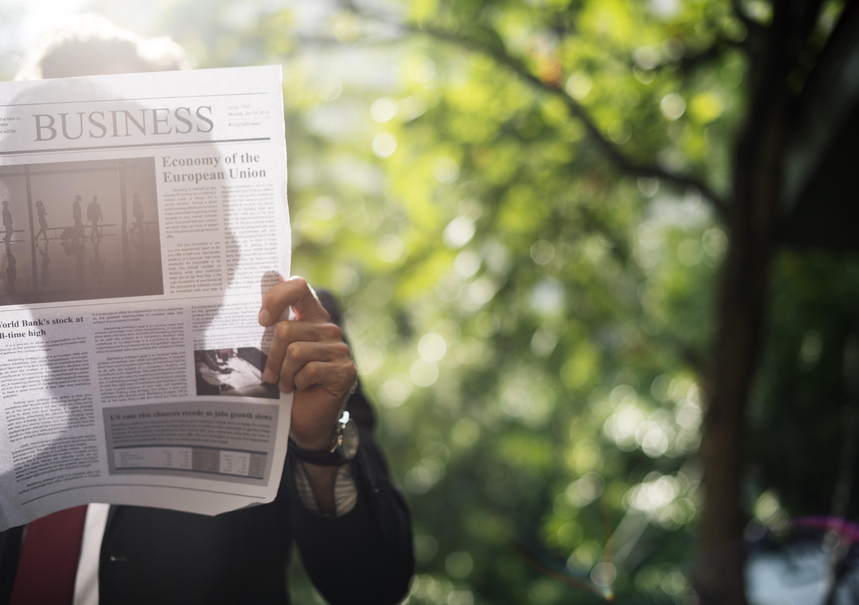 A businessman reading a newspaper in a park