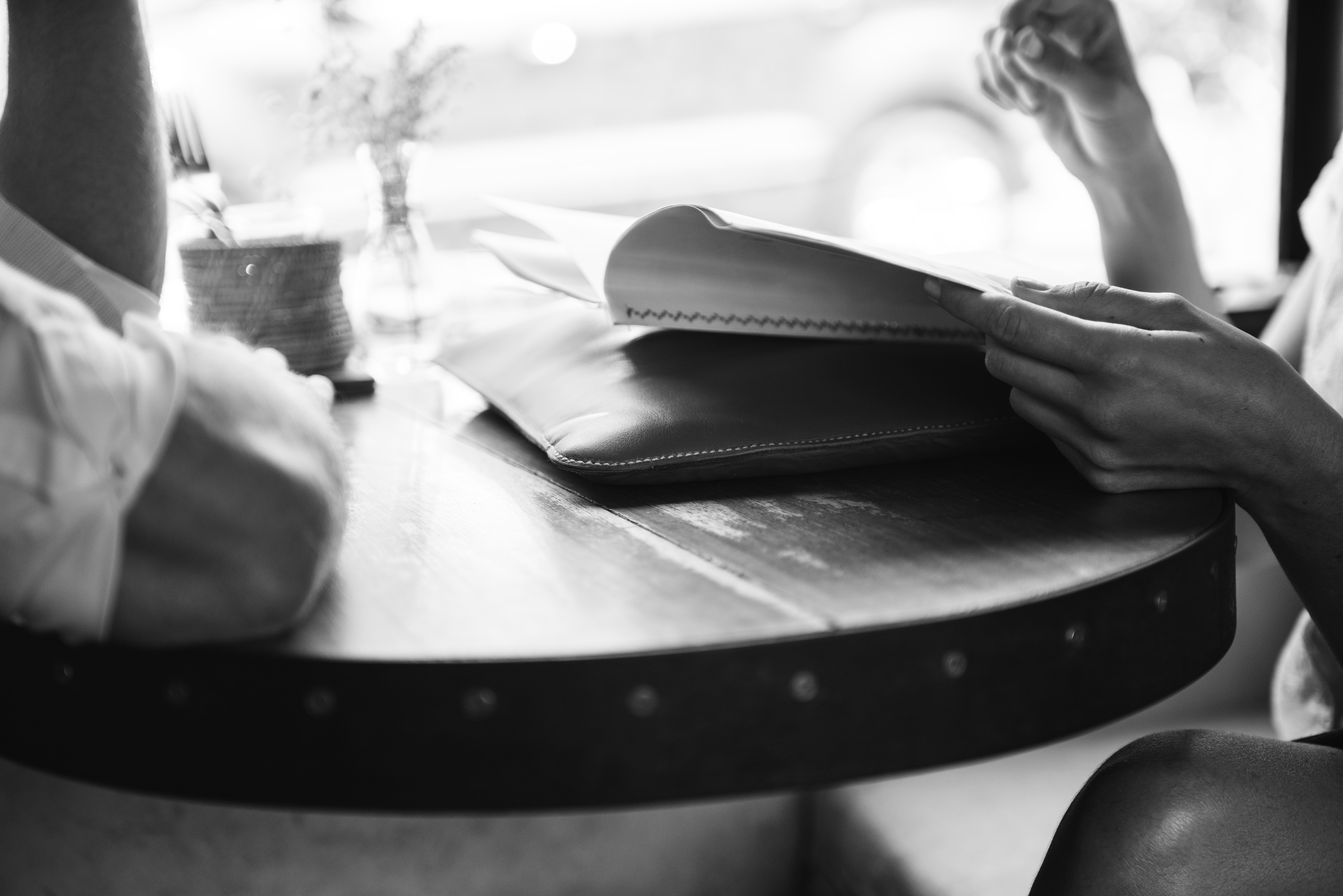 People sit at a cafe table reading and catching up