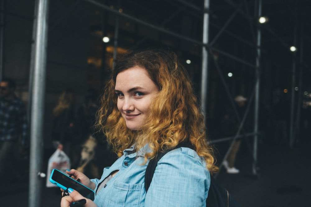 woman holding black smartphone near gray metal frame at daytime