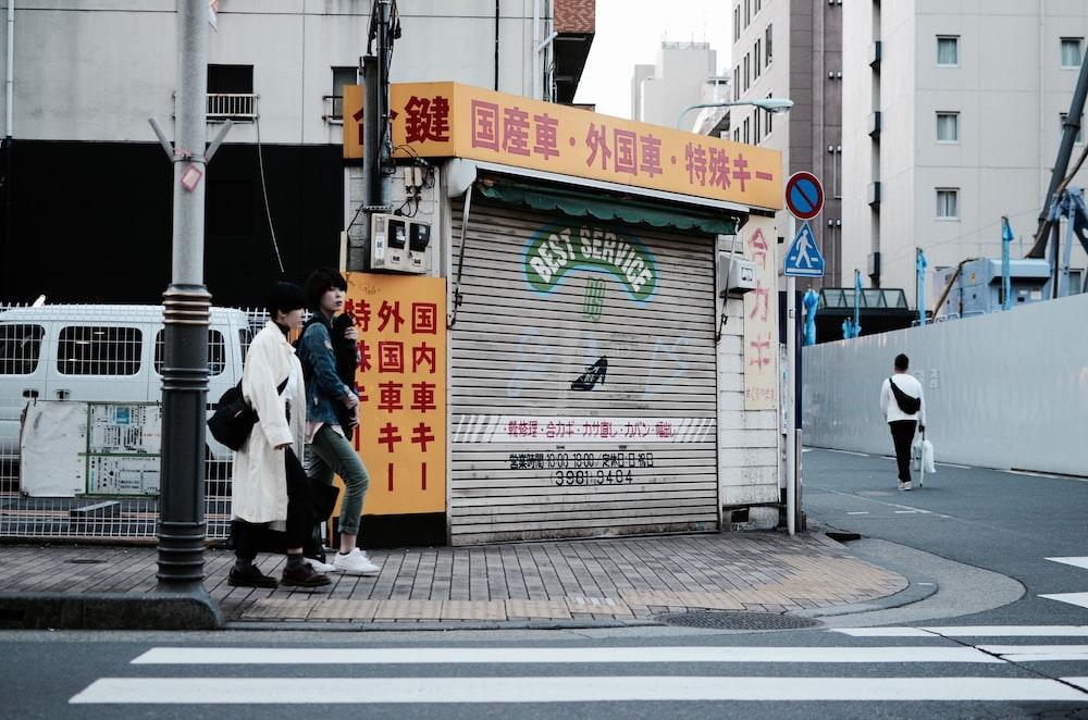 two women walking near street post and pedestrian lane