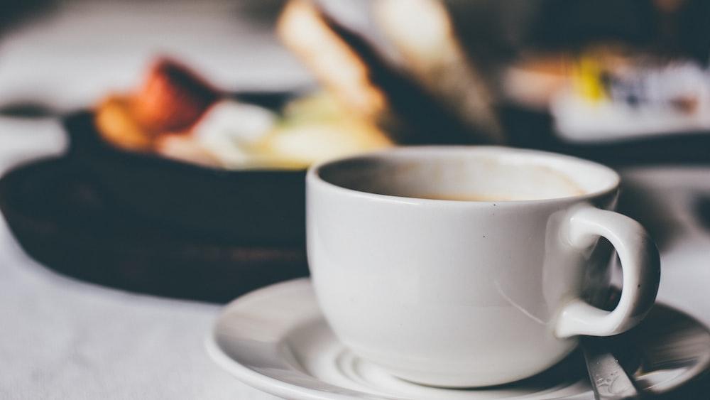 white ceramic mug on saucer
