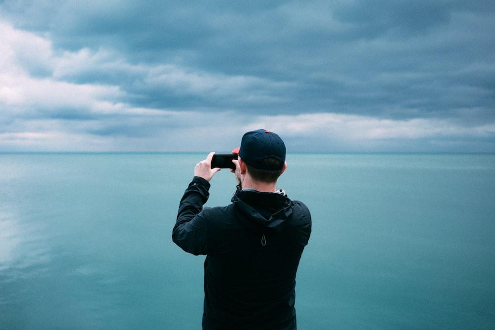 men's black hoodie in front of teal sea