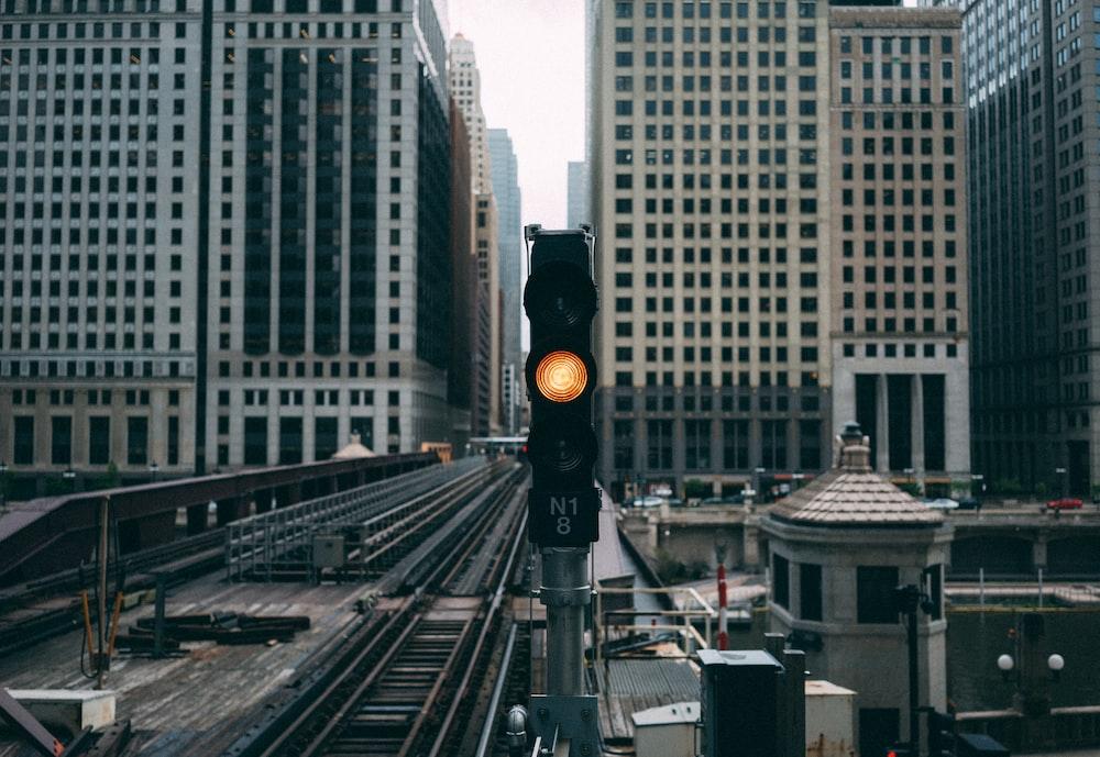 ready traffic light near railroad between buildings