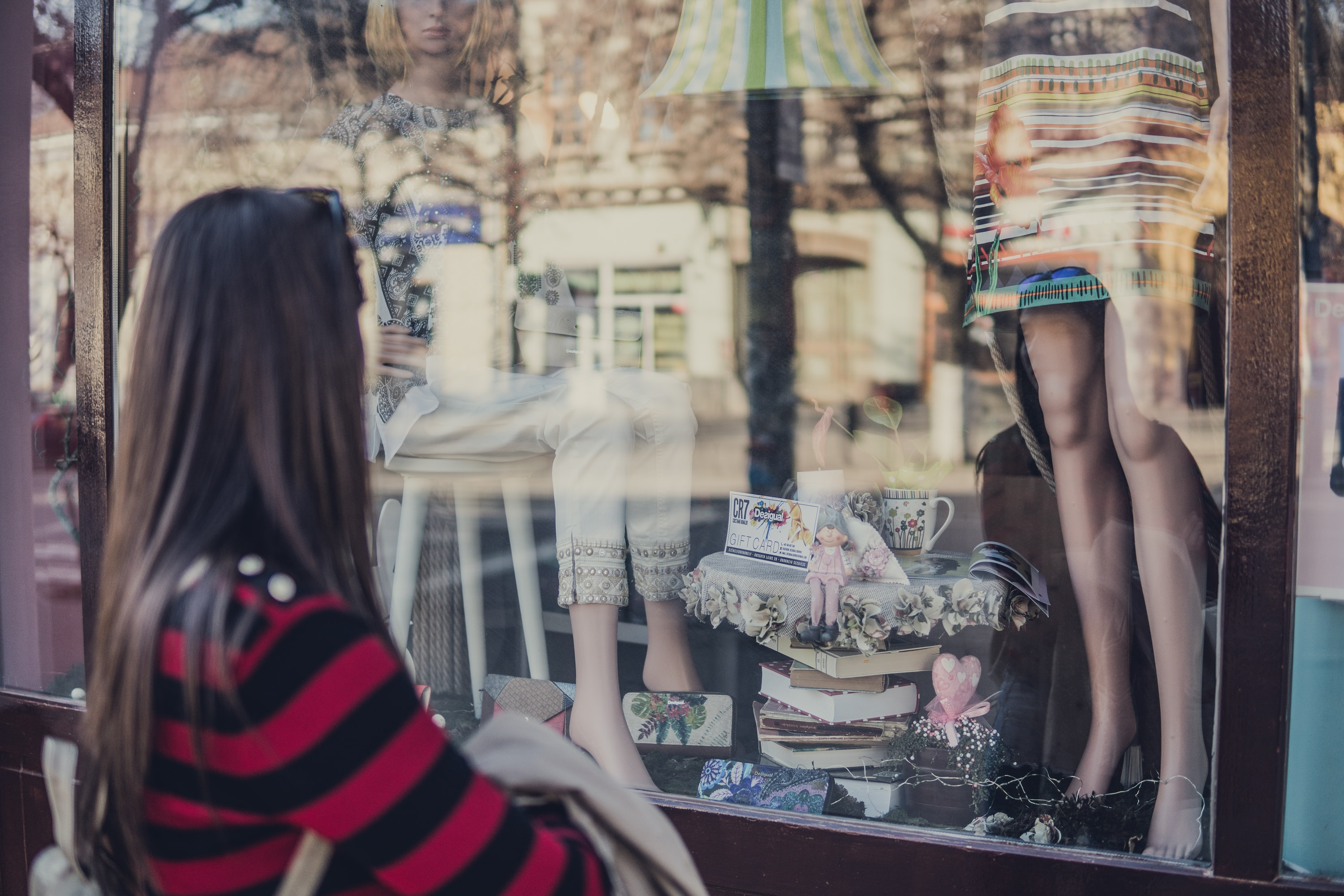 A woman looking at mannequins in a storefront