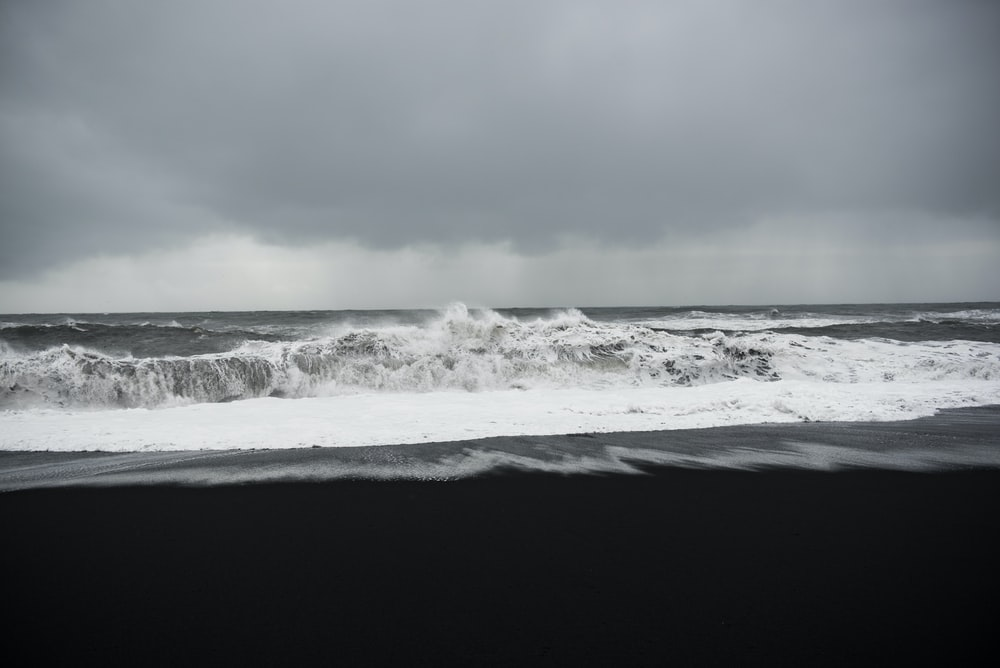 grayscale photo of shore under clouds