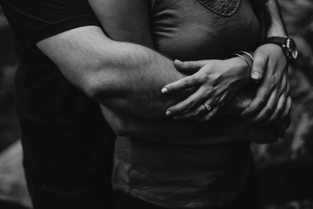 grayscale photo of man hugging a woman