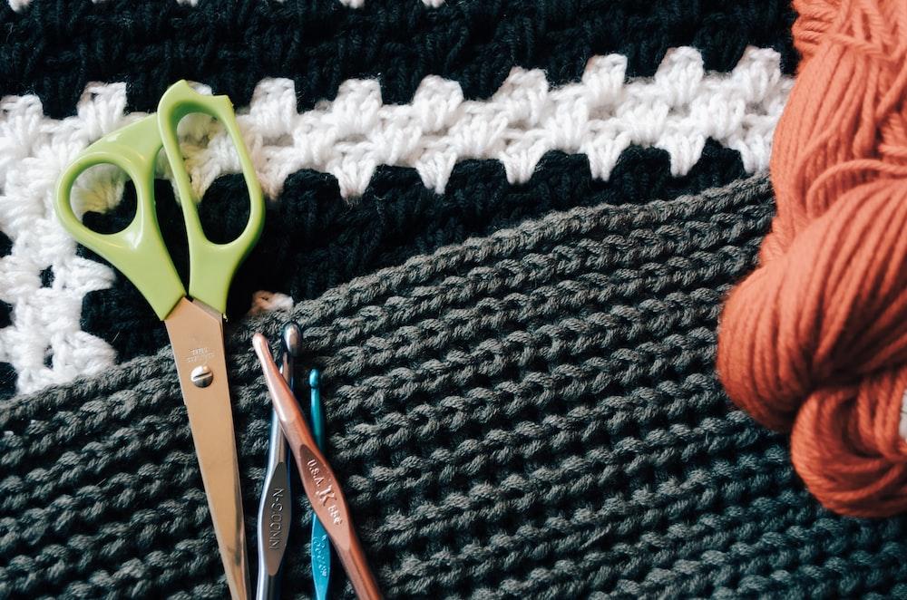 green scissors besides knitting sticks
