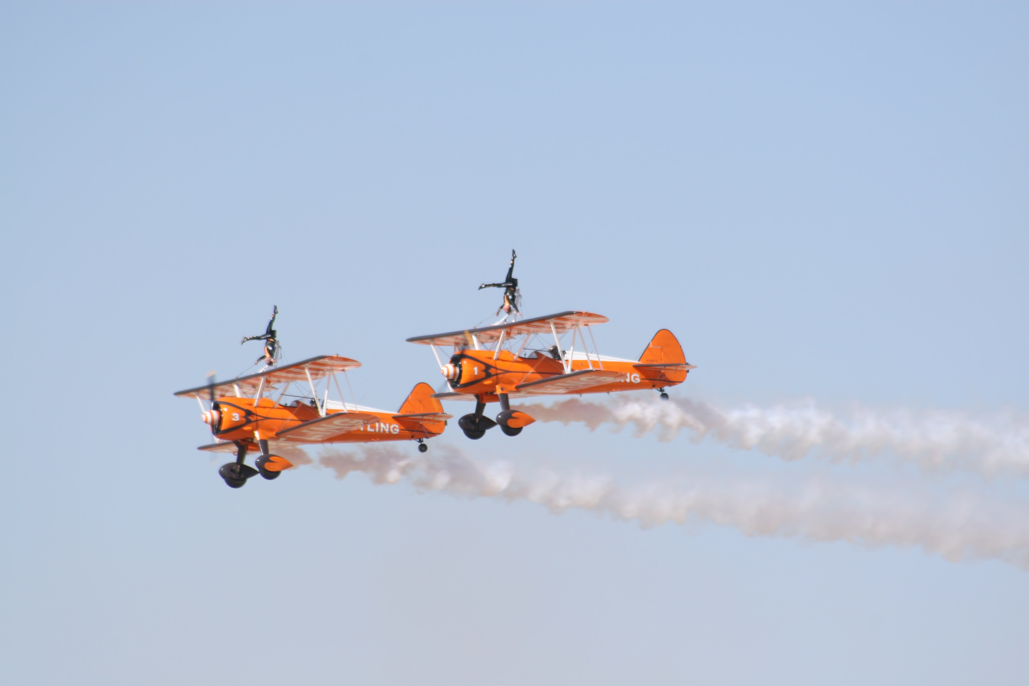 photo of two orange flying biplanes