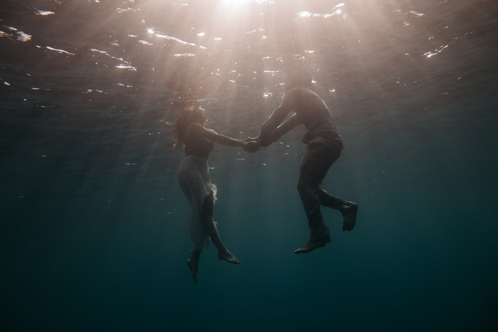 underwater photography of woman and man while holding hands