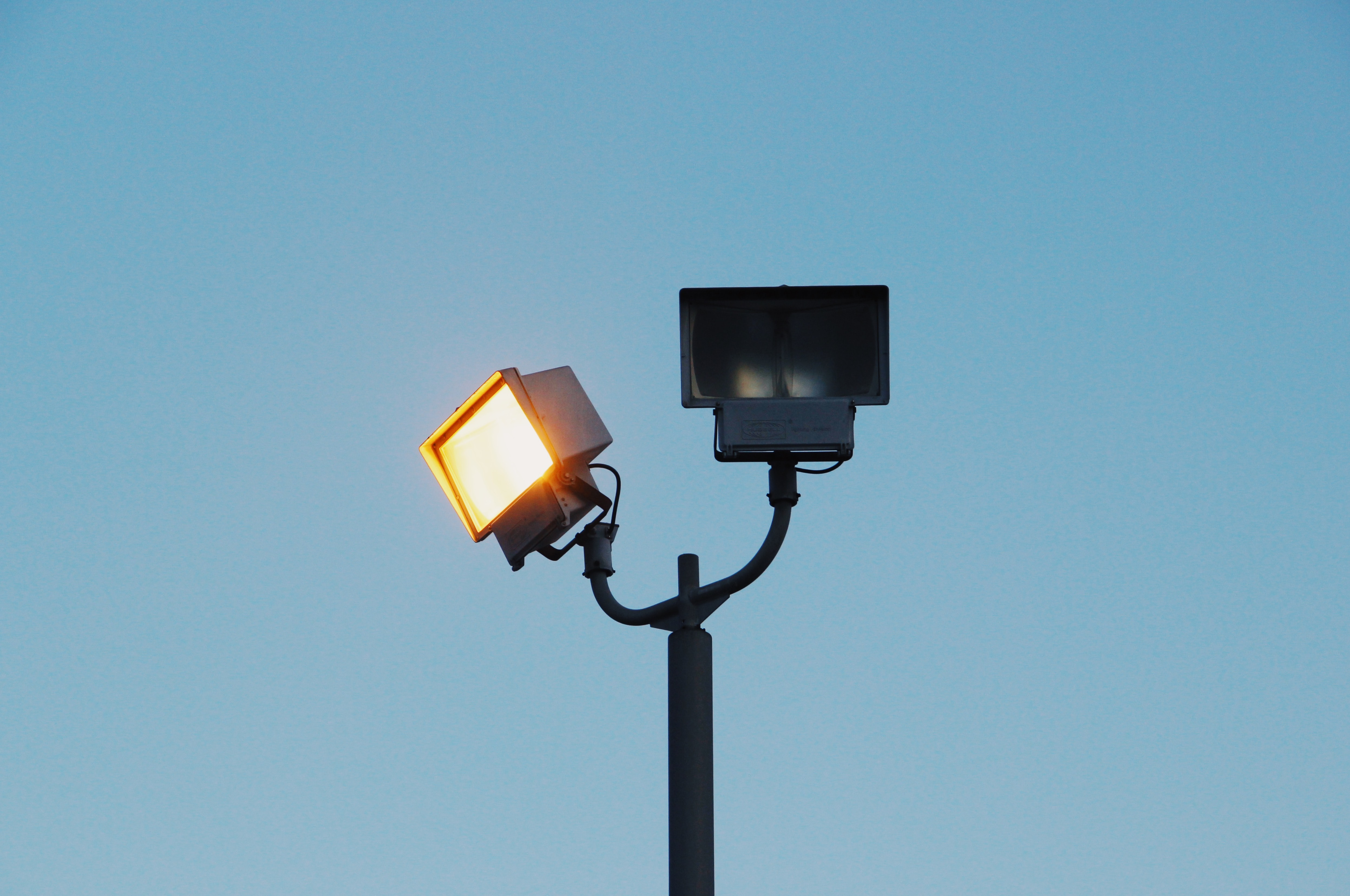 A rectangular spot light on a post next to another unlit lamp