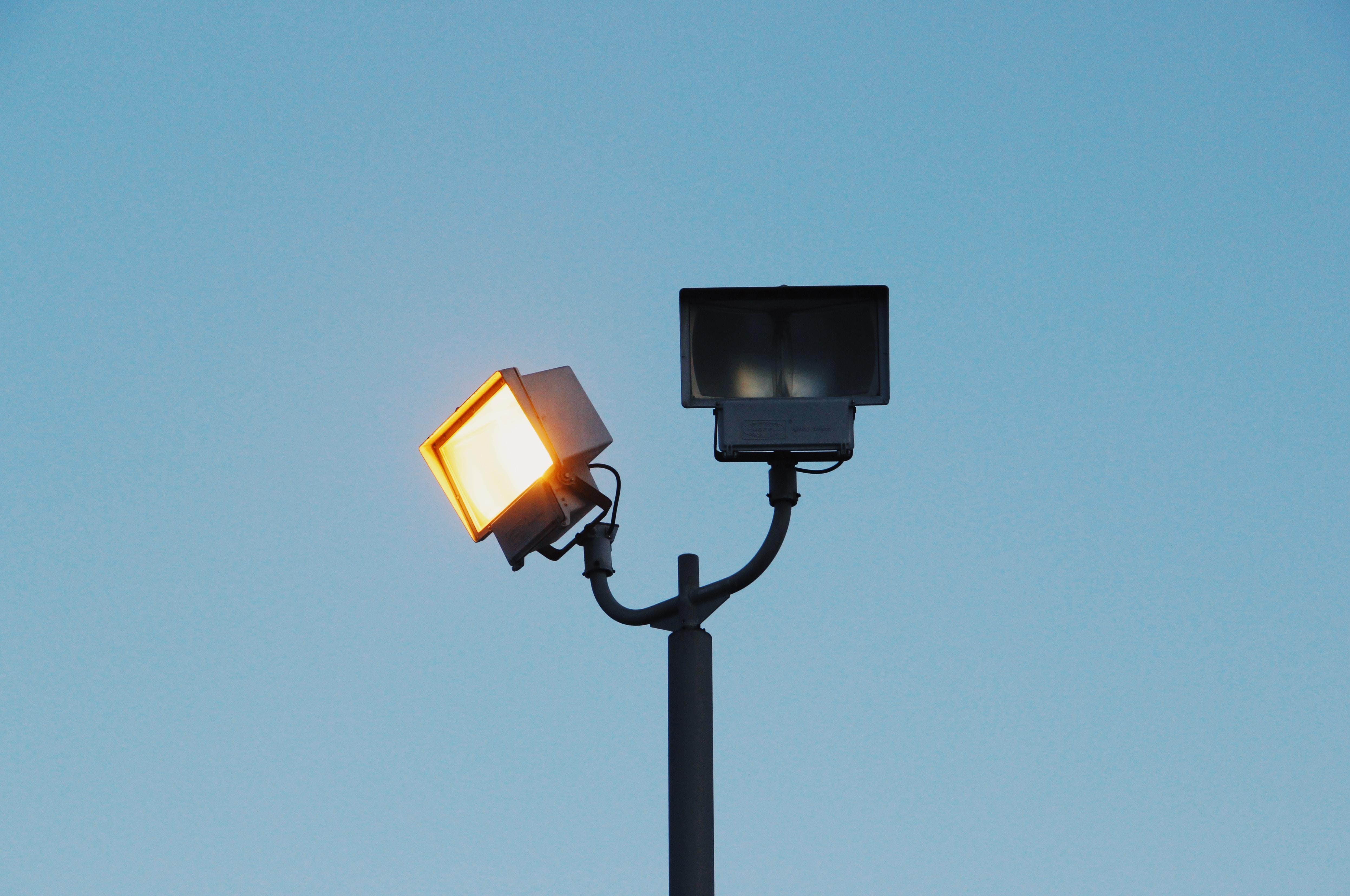 A rectangular spot light on a post next to another unlit lamp