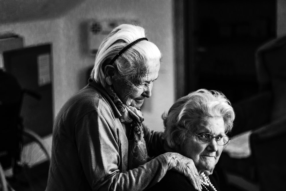 A standing elderly woman rests her hands on the shoulders of another woman