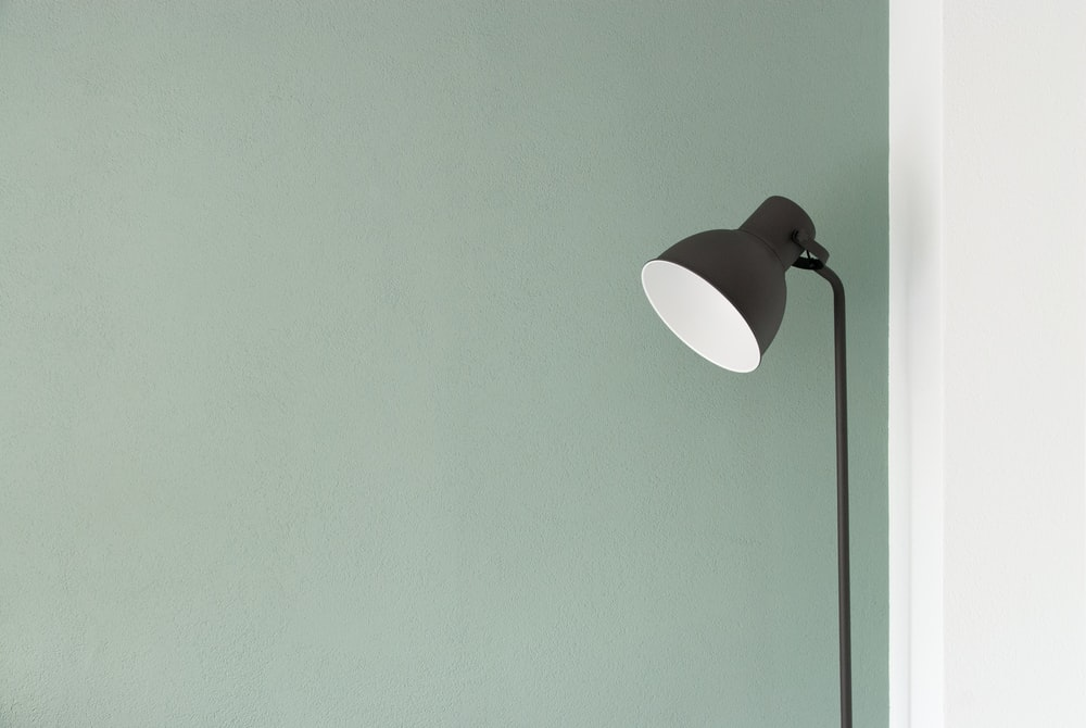A floor lamp against a pastel green wall