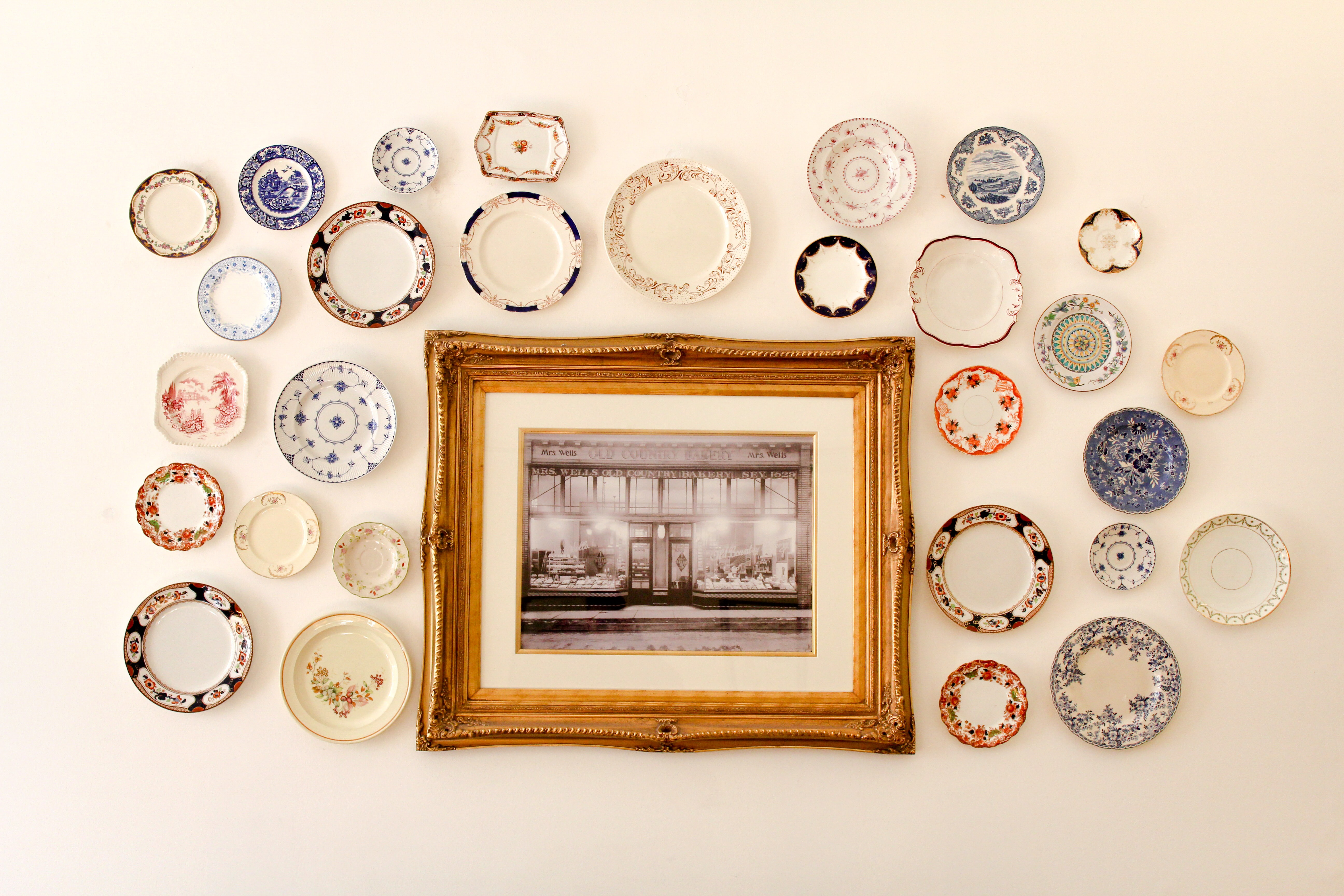 Photo in a wooden frame surrounded by colorful decorative plates all hanging on a white wall