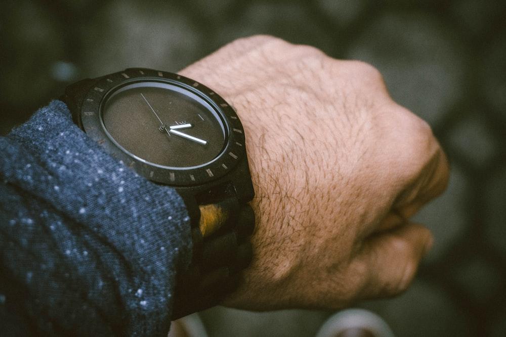 round black analog watch in left human wrist