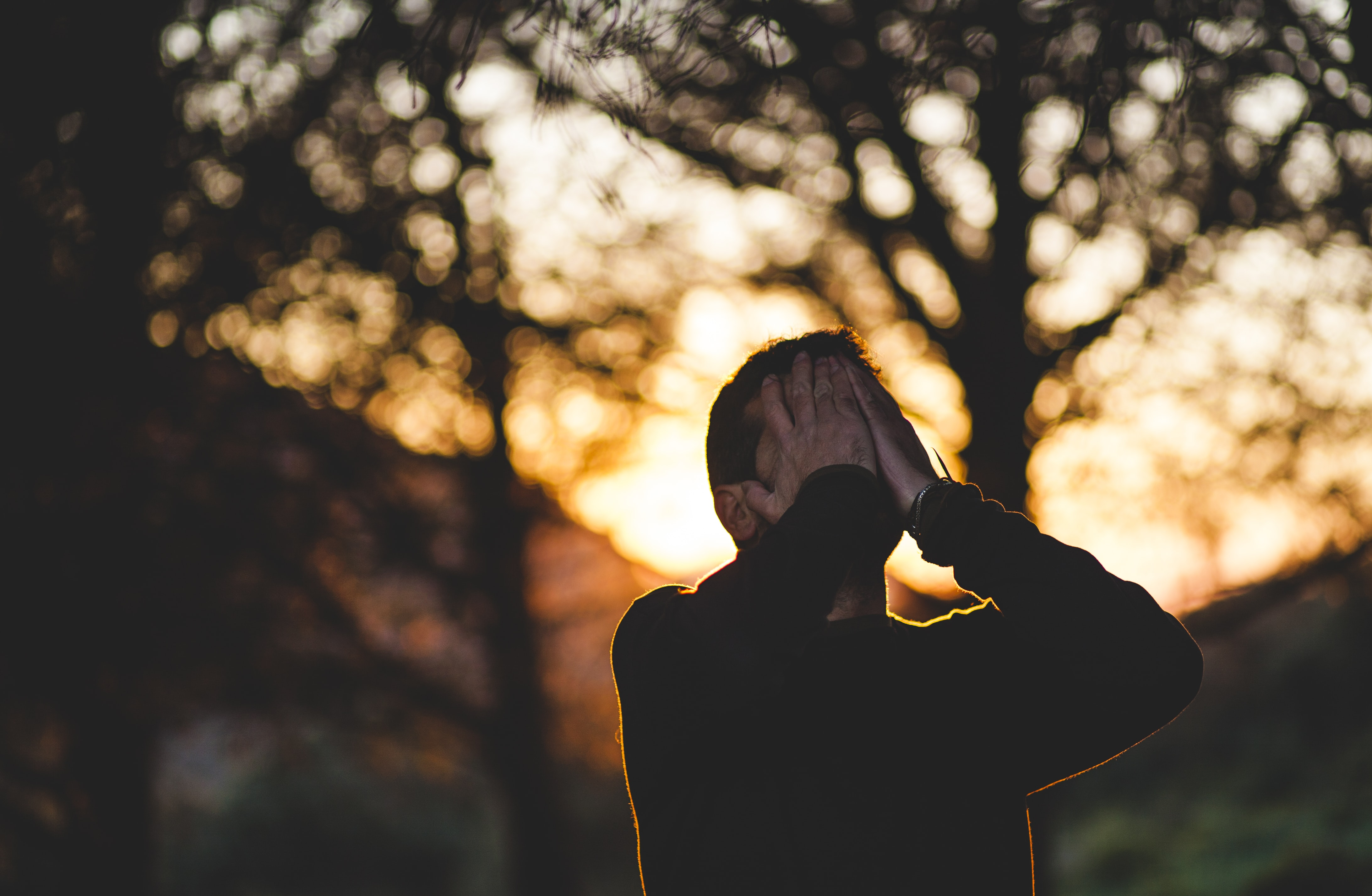 A man holds his hands over his face in front of trees at sunset