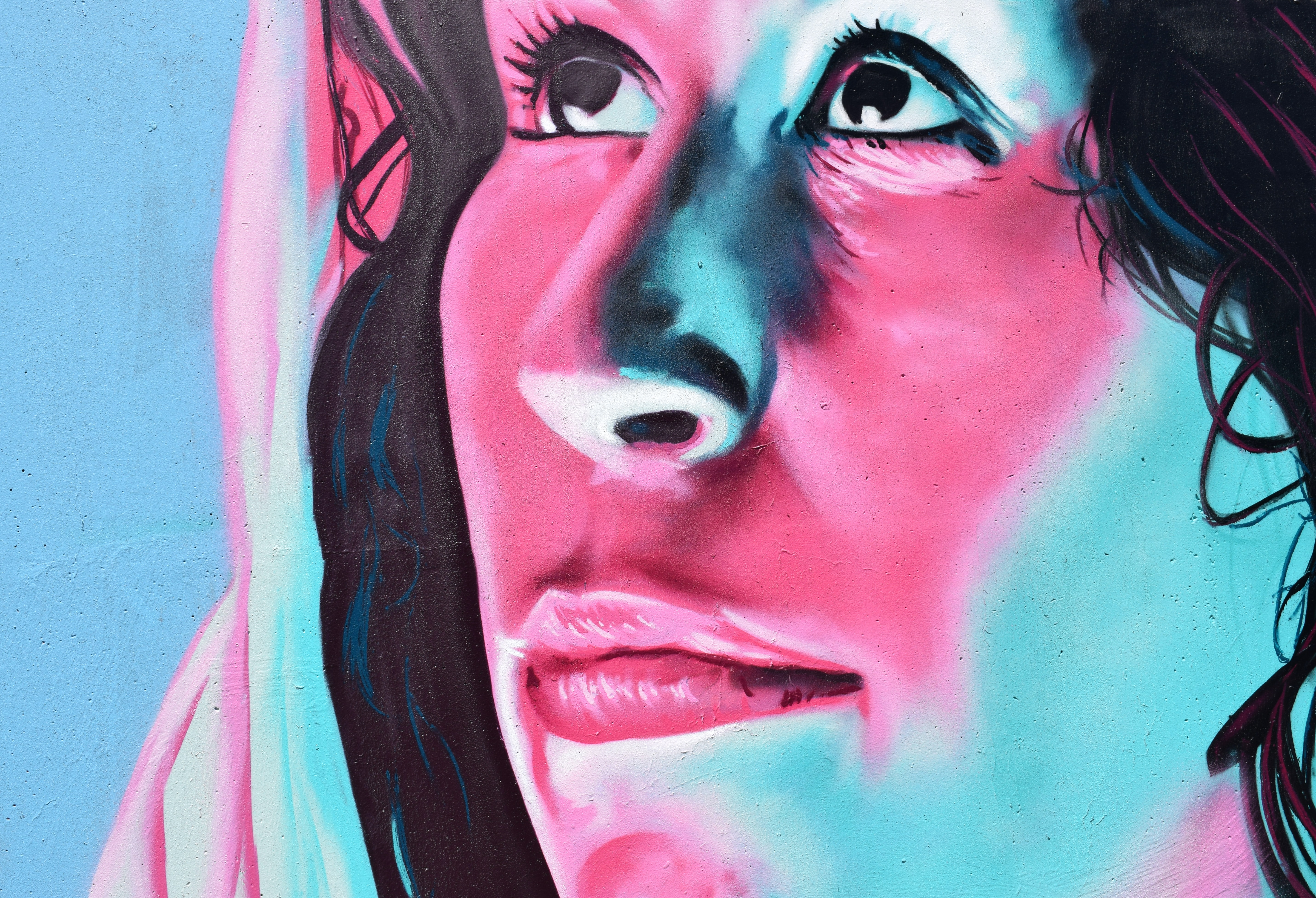 A mural of a woman's face in pink, blue, and black
