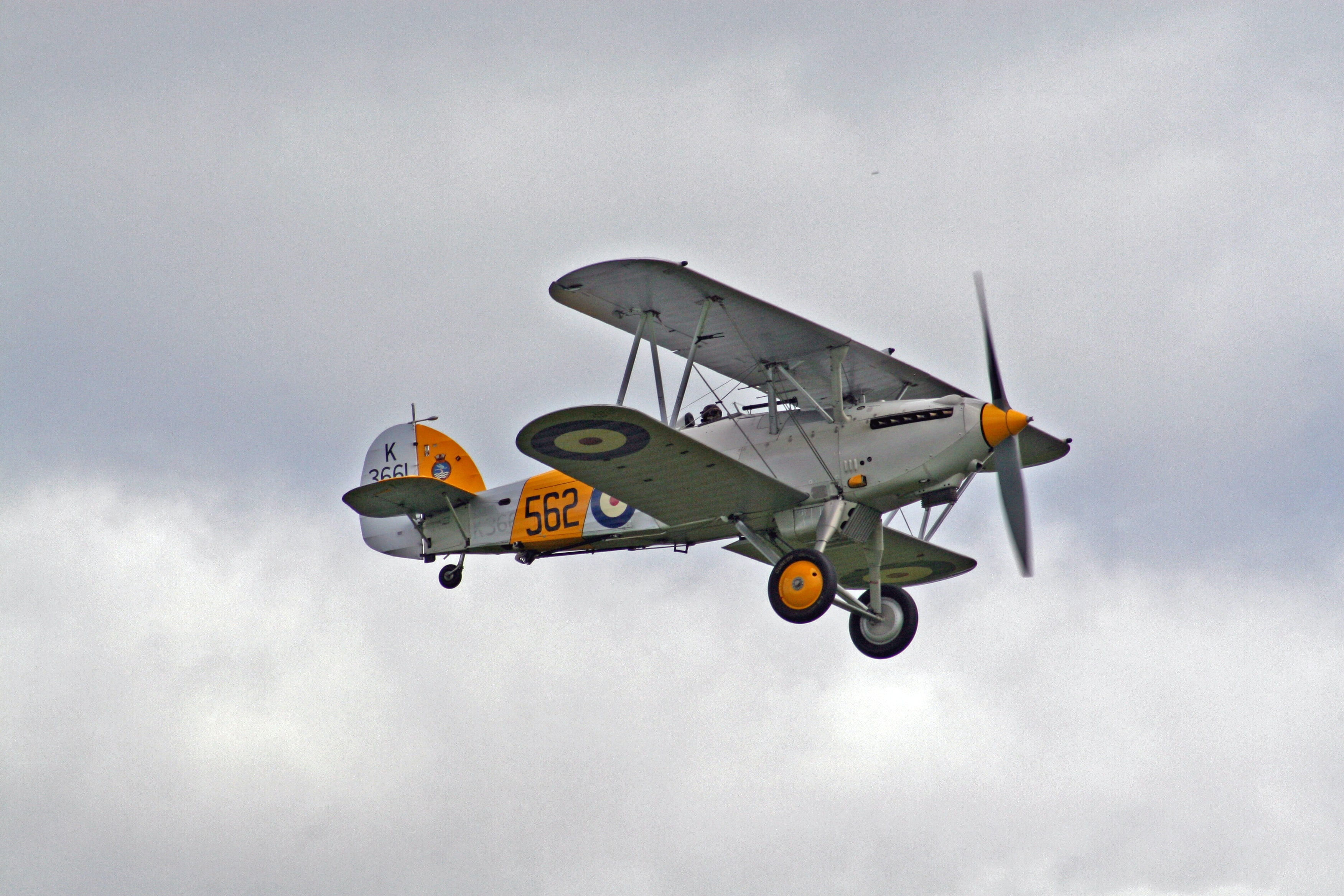 white and orange bi-plane in mid air