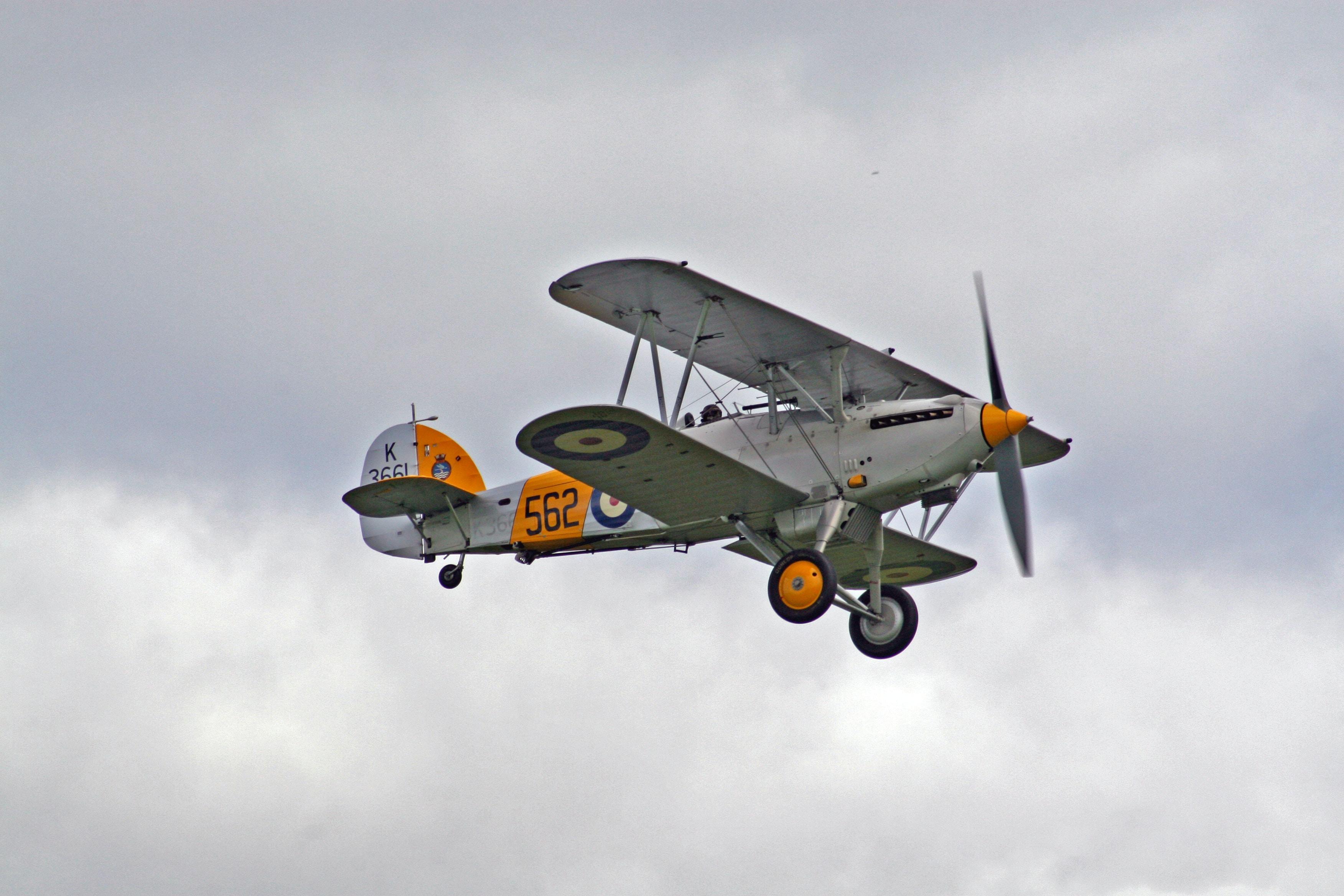 white and orange bi-plane in mid air