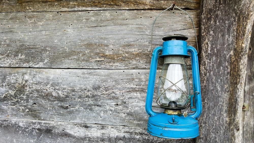 blue kerosene lamp hanging on wooden wall