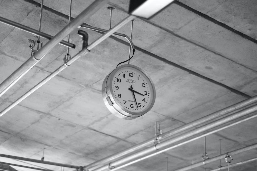 round grey stainless steel analog clock displaying 3:22