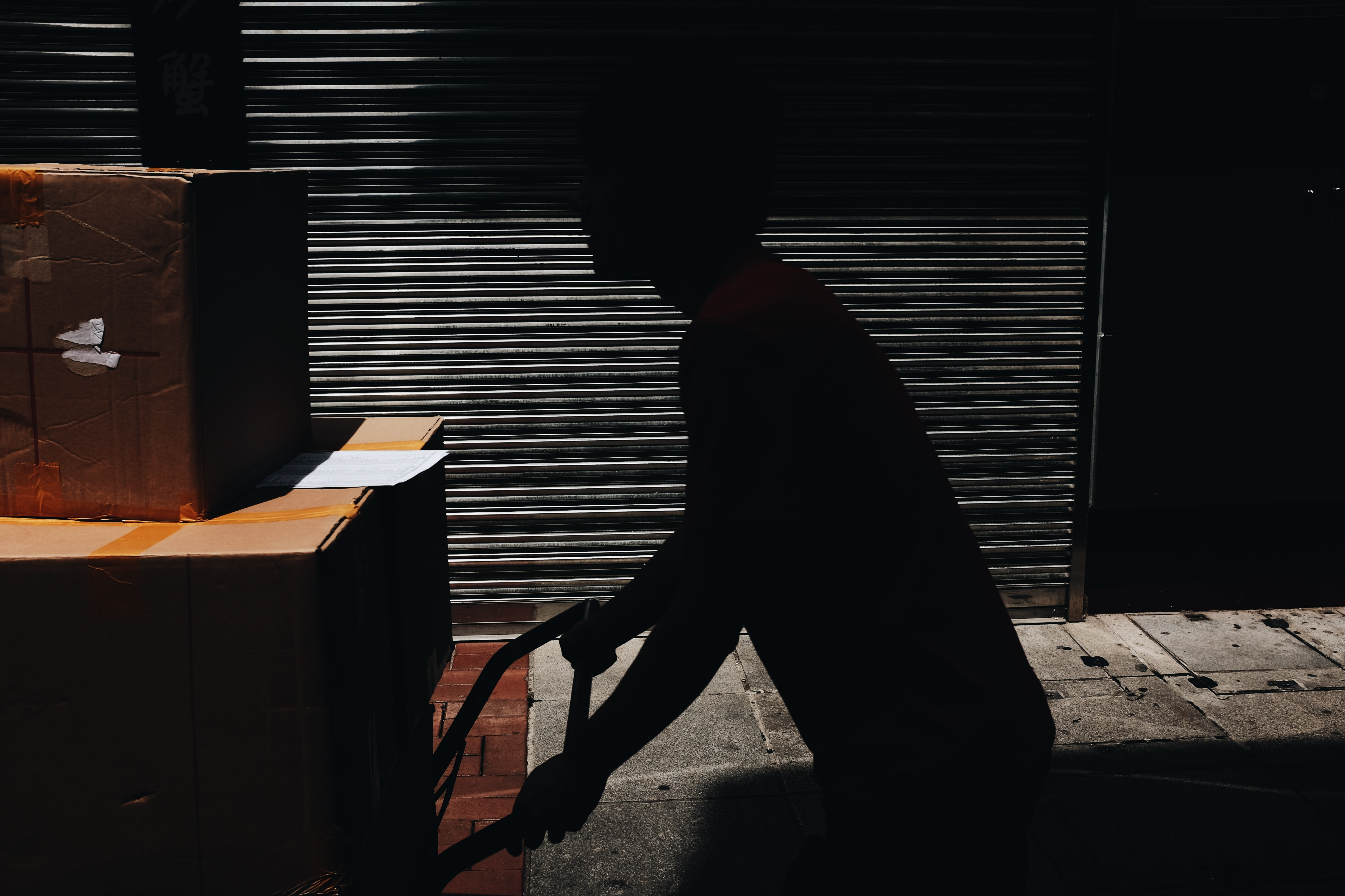 A silhouette of a person pushing a cart with cardboard boxes
