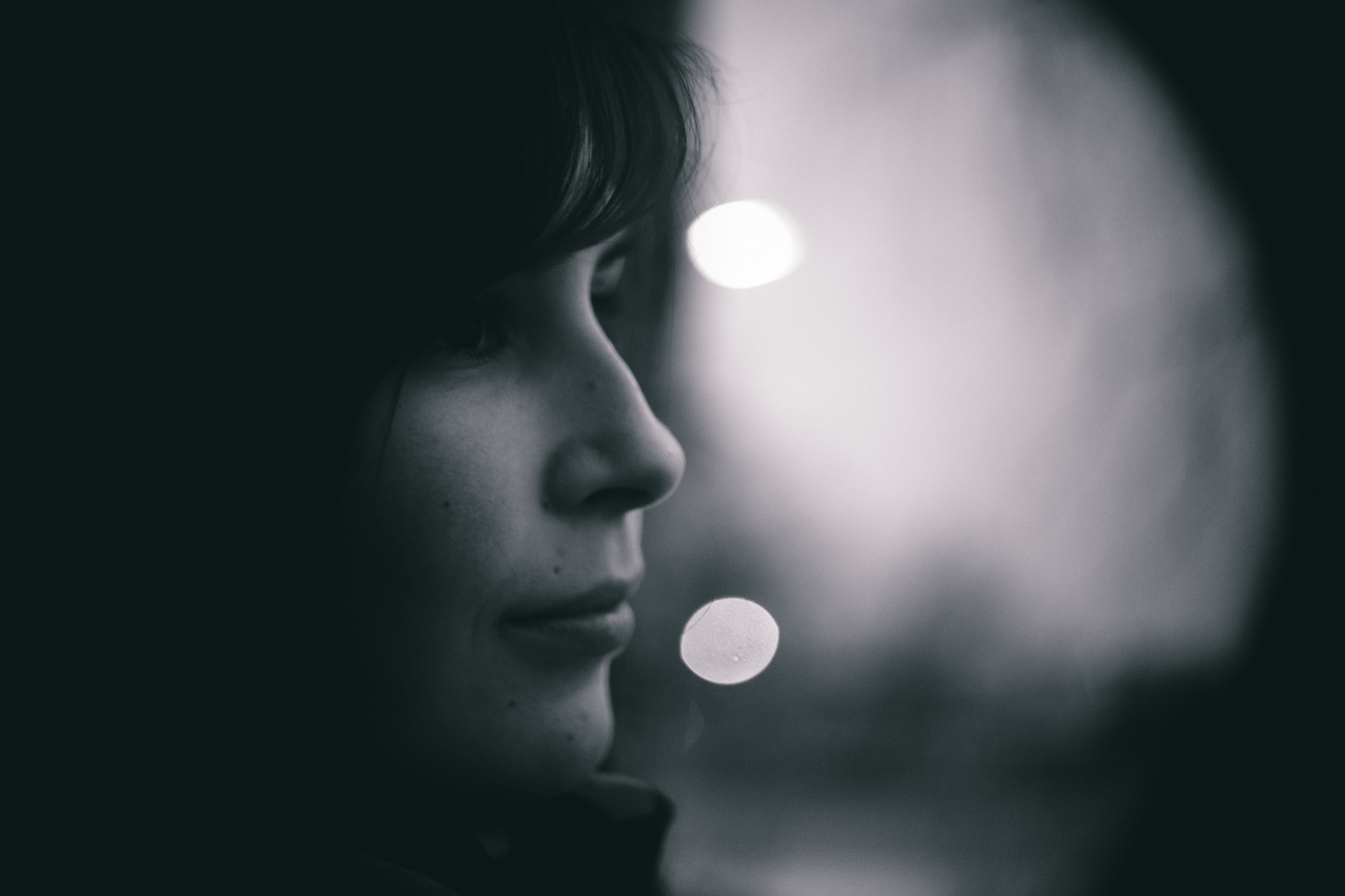 Profile of a woman's face in the shadows surrounded by bokeh lights