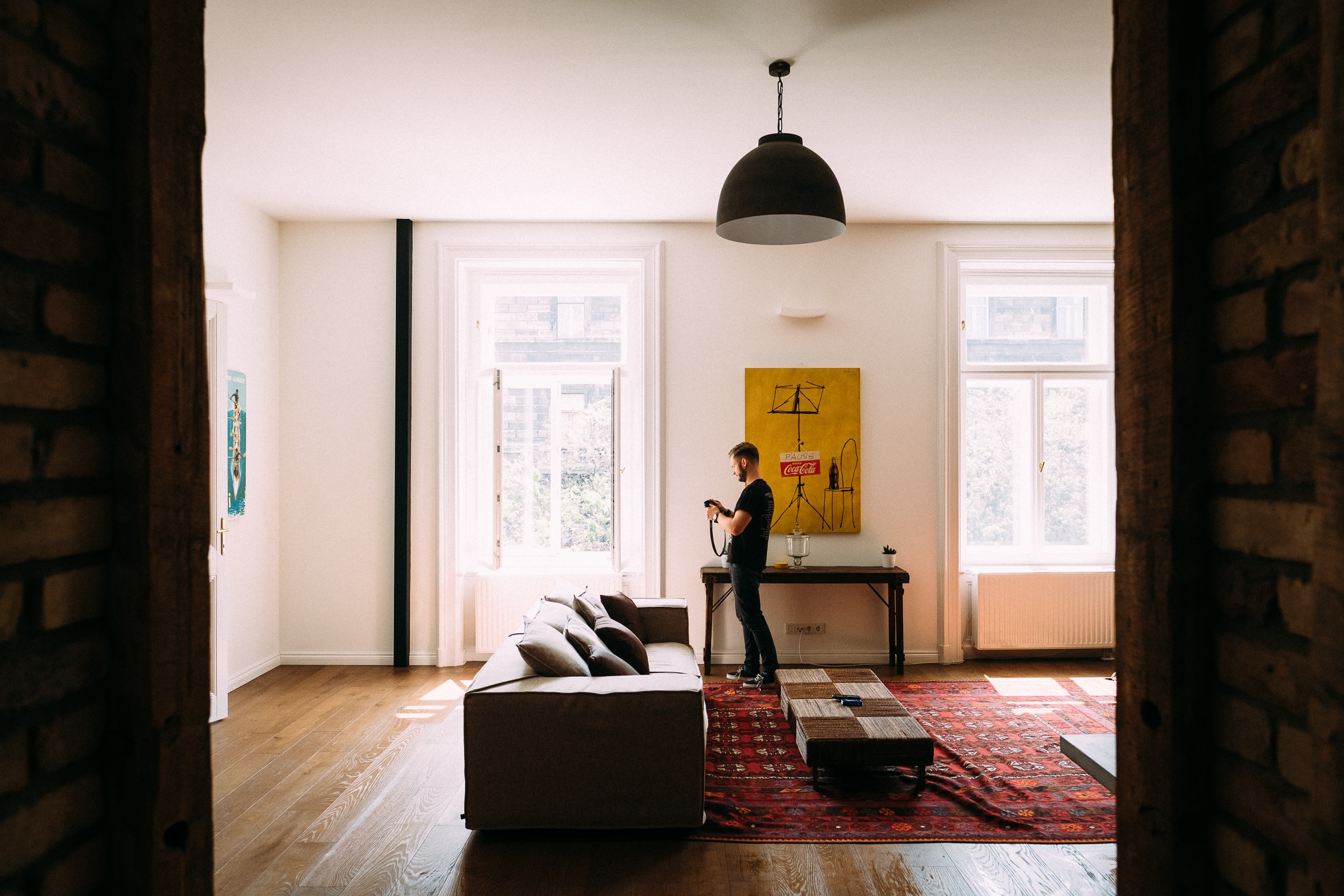 Man stands in bright living room near couch and low table in front of poster