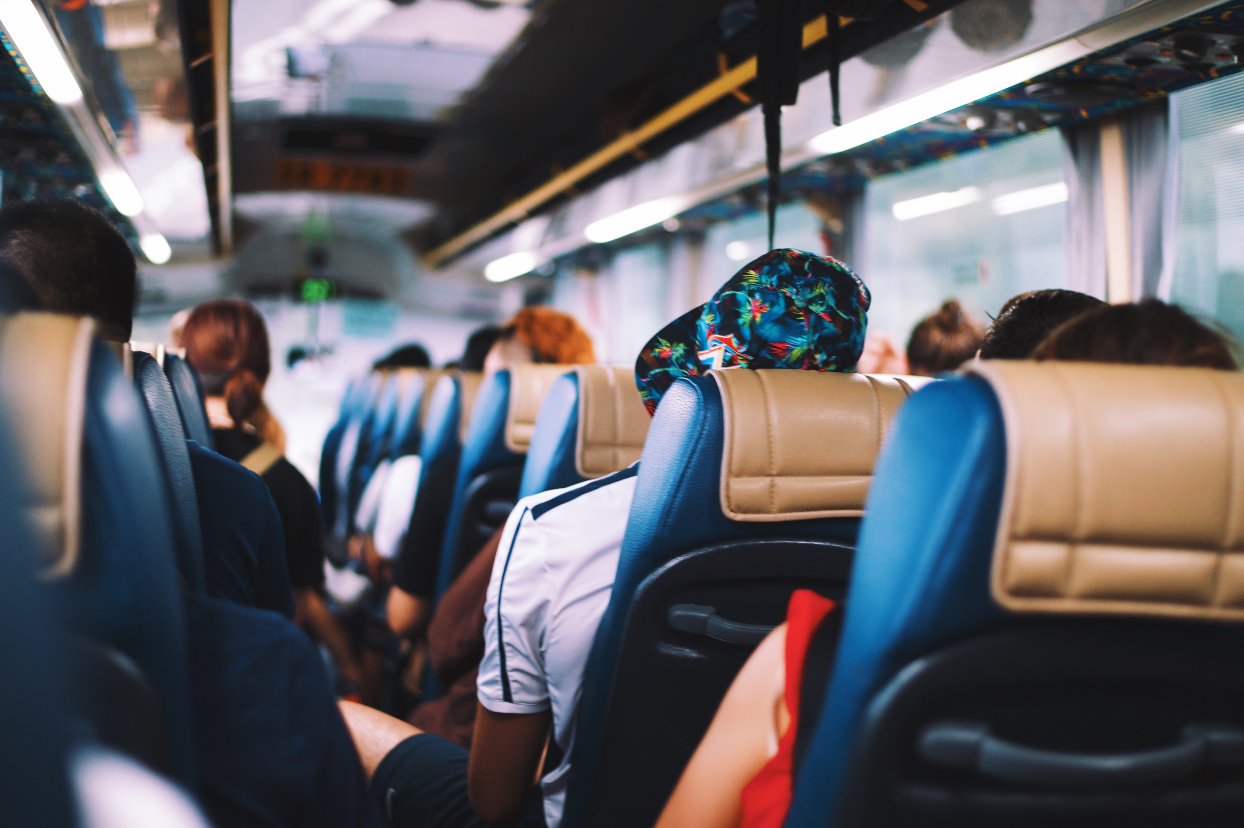 A back-to-front shot of a bus full of people in blue and tan seats