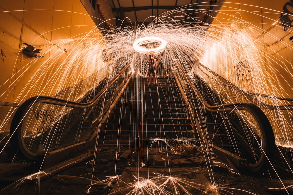 steel wool photography of man standing on stairs