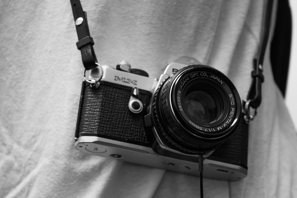 person holding black and gray film camera with sling