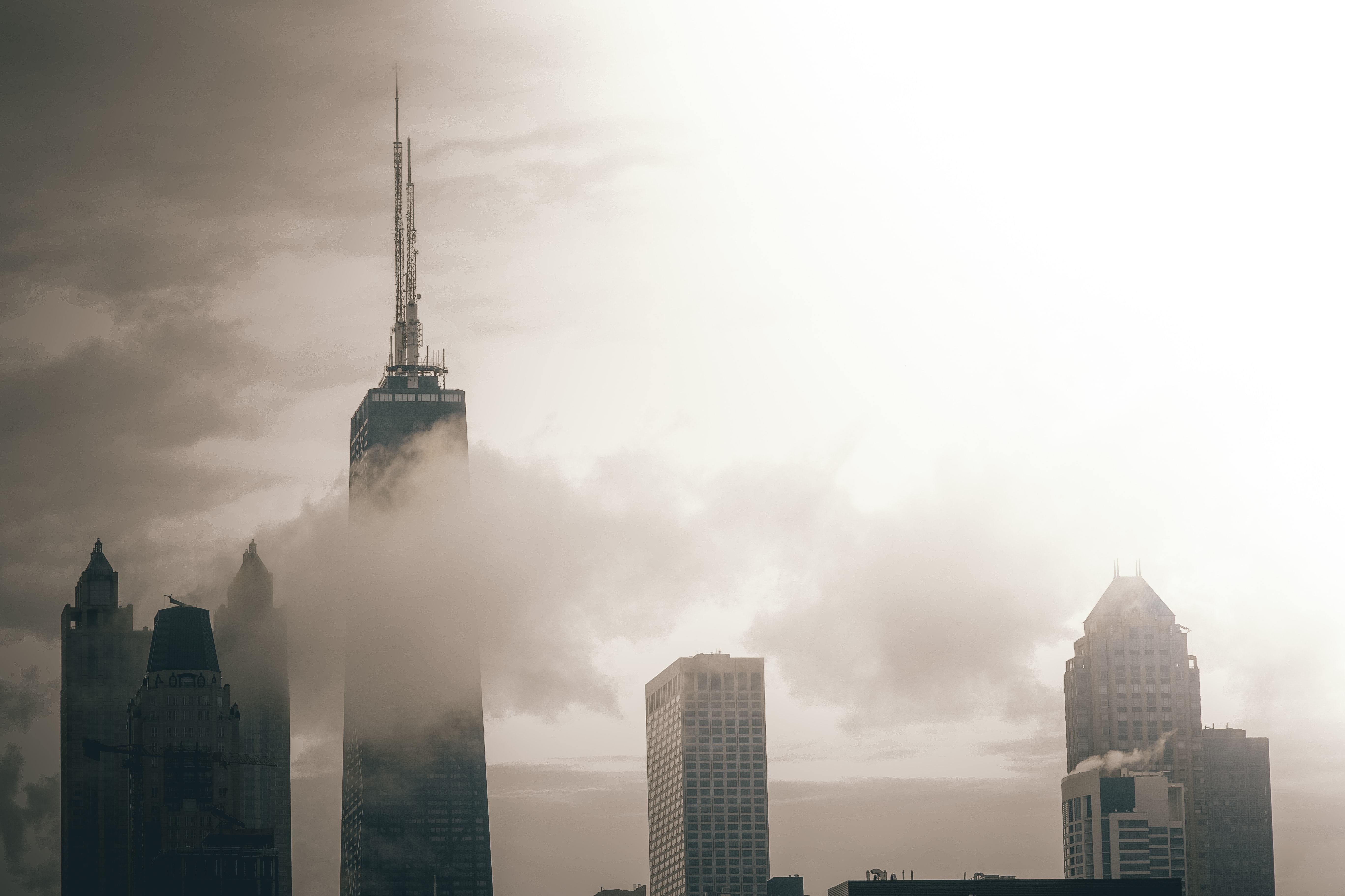 Black and white Chicago cityscape with the tallest building half covered by a cloud