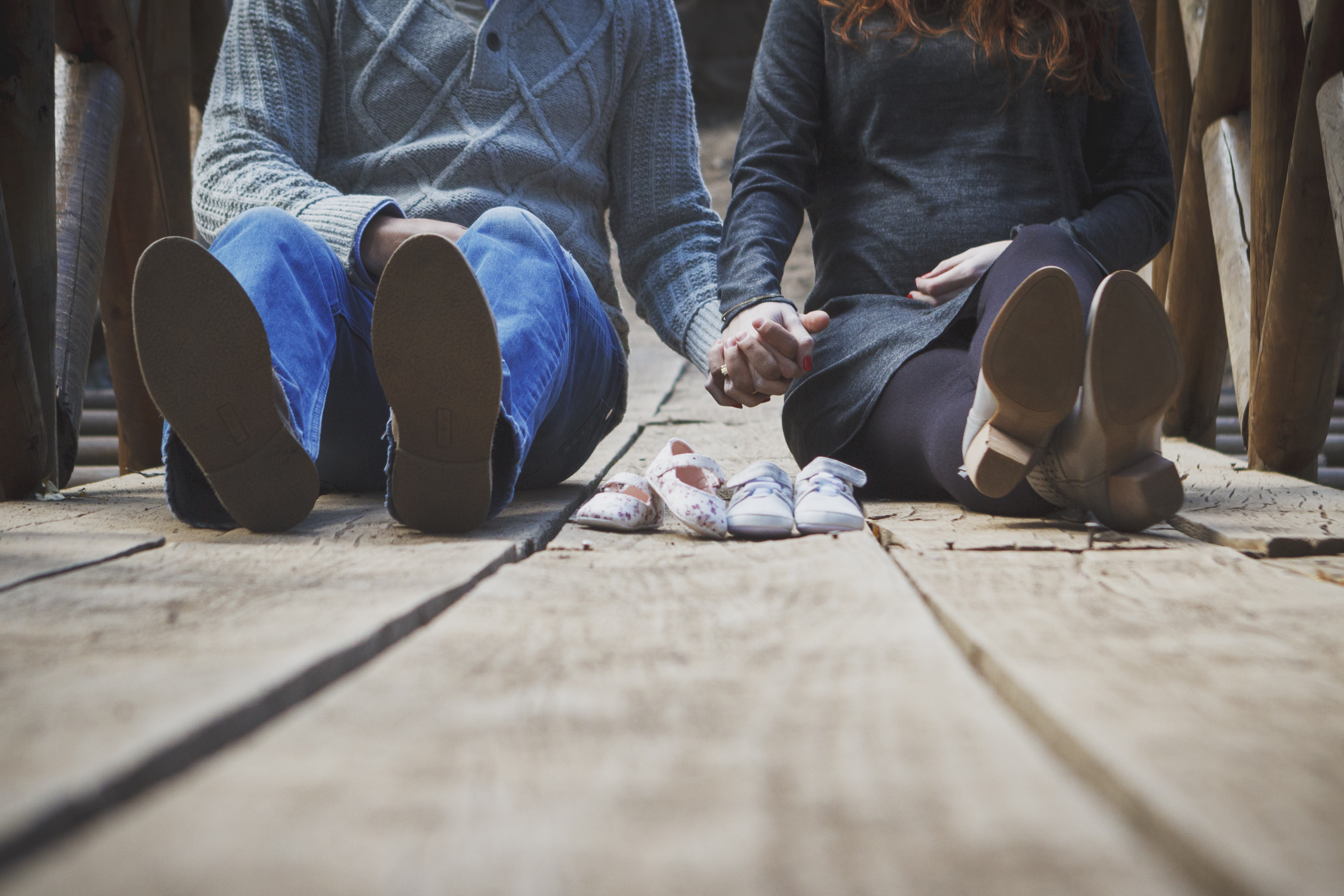 couple sitting on wooden walkway with pair of shoes in between them